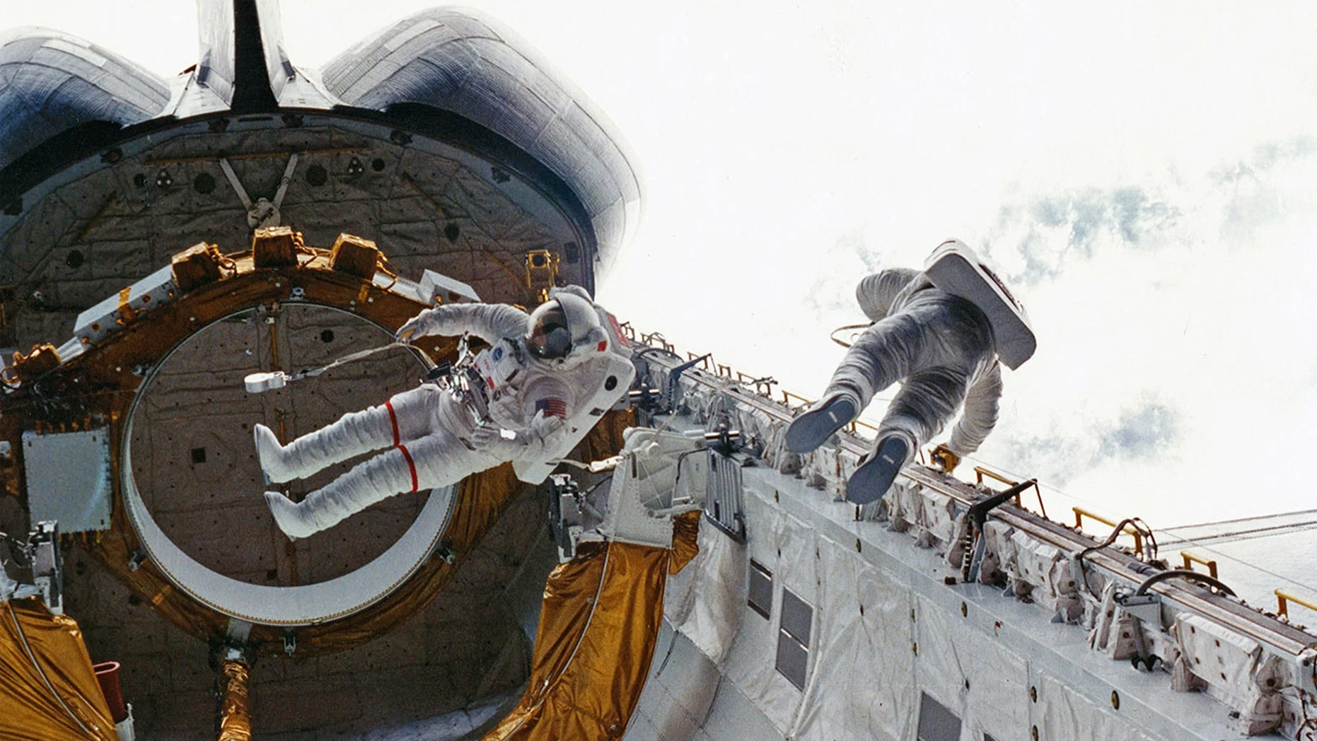 STS-6 crewmates Don Peterson (at right) and Story Musgrave perform the first shuttle-era spacewalk outside Challenger in 1983. (Credit: NASA)