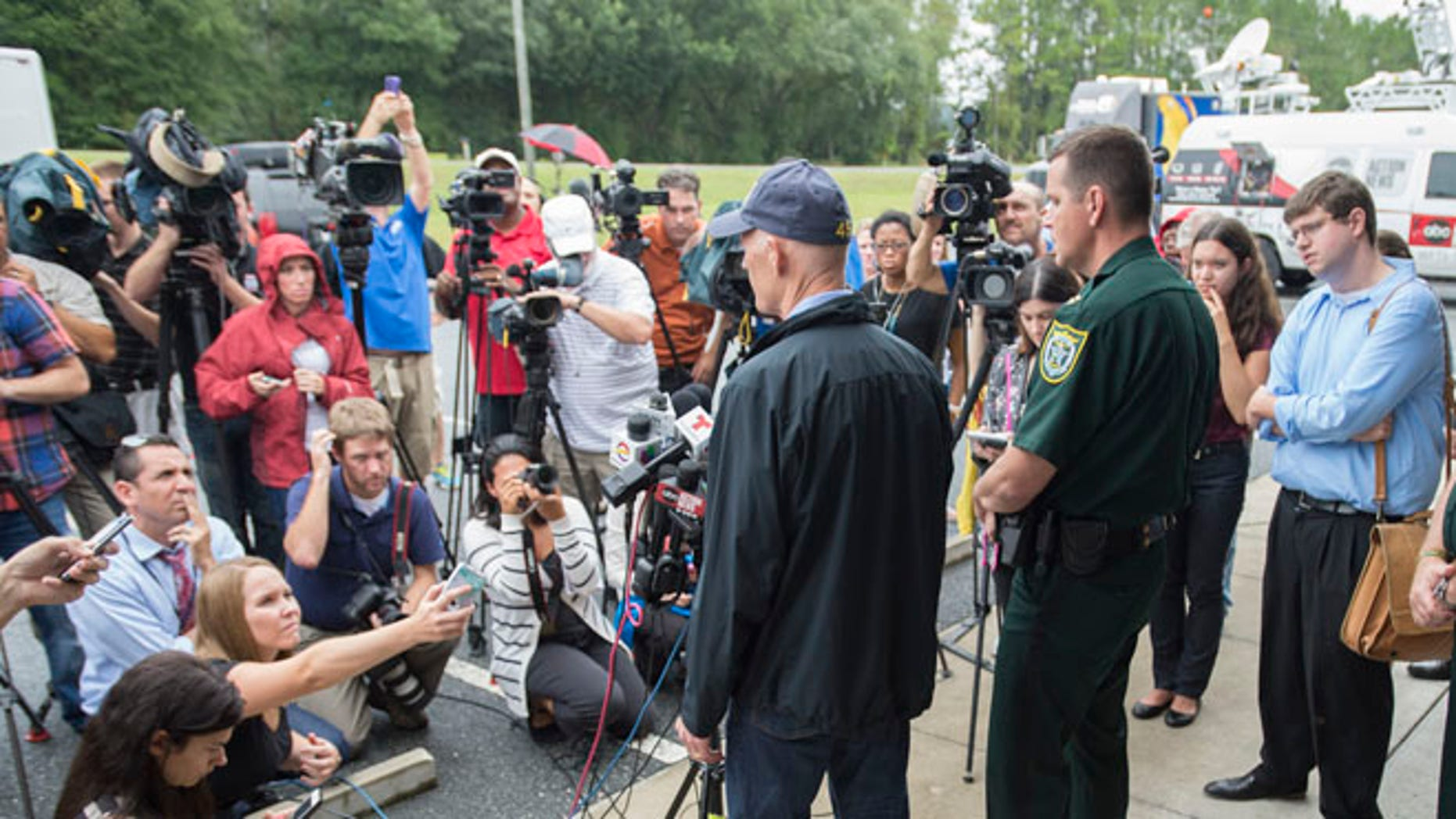 Sept. 19, 2014: Florida Gov. Rick Scott, left, and Gilcrist county sheriff Robert Schultz, right, talk to the media