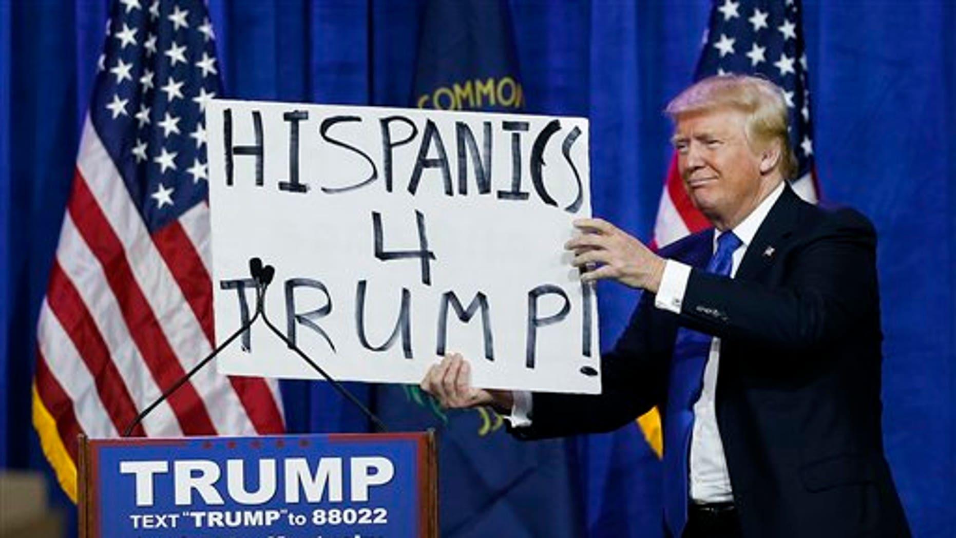 """El precandidato presidencial republicano Donald Trump sostiene un cartel que dice """"Hispanos con Trump"""" y que cargaba un espectador durante un mitin el martes 1 de marzo de 2016 en Louisville, Kentucky. (Foto AP/John Bazemore)"""