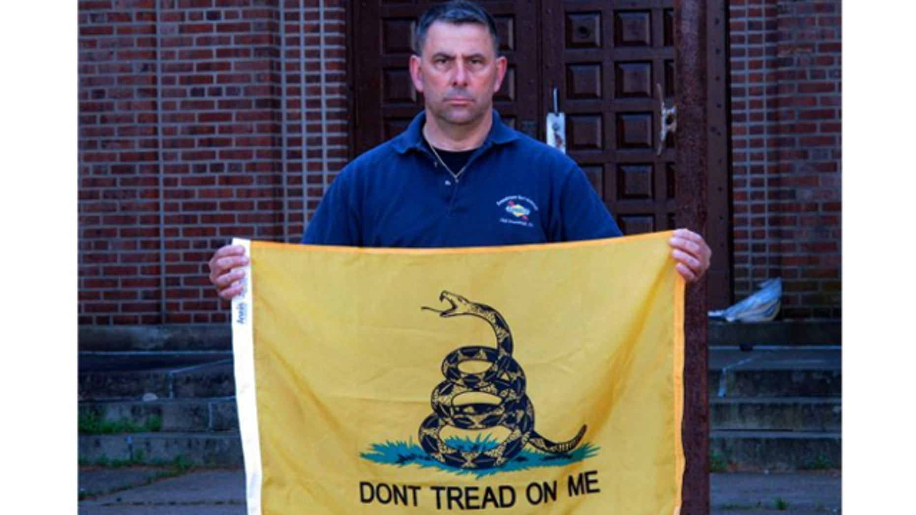 April 26, 2013: Peter Parente, president of the United Veterans Memorial and Patriotic Association, holds a Gadsden flag outside an armory in New Rochelle, N.Y.