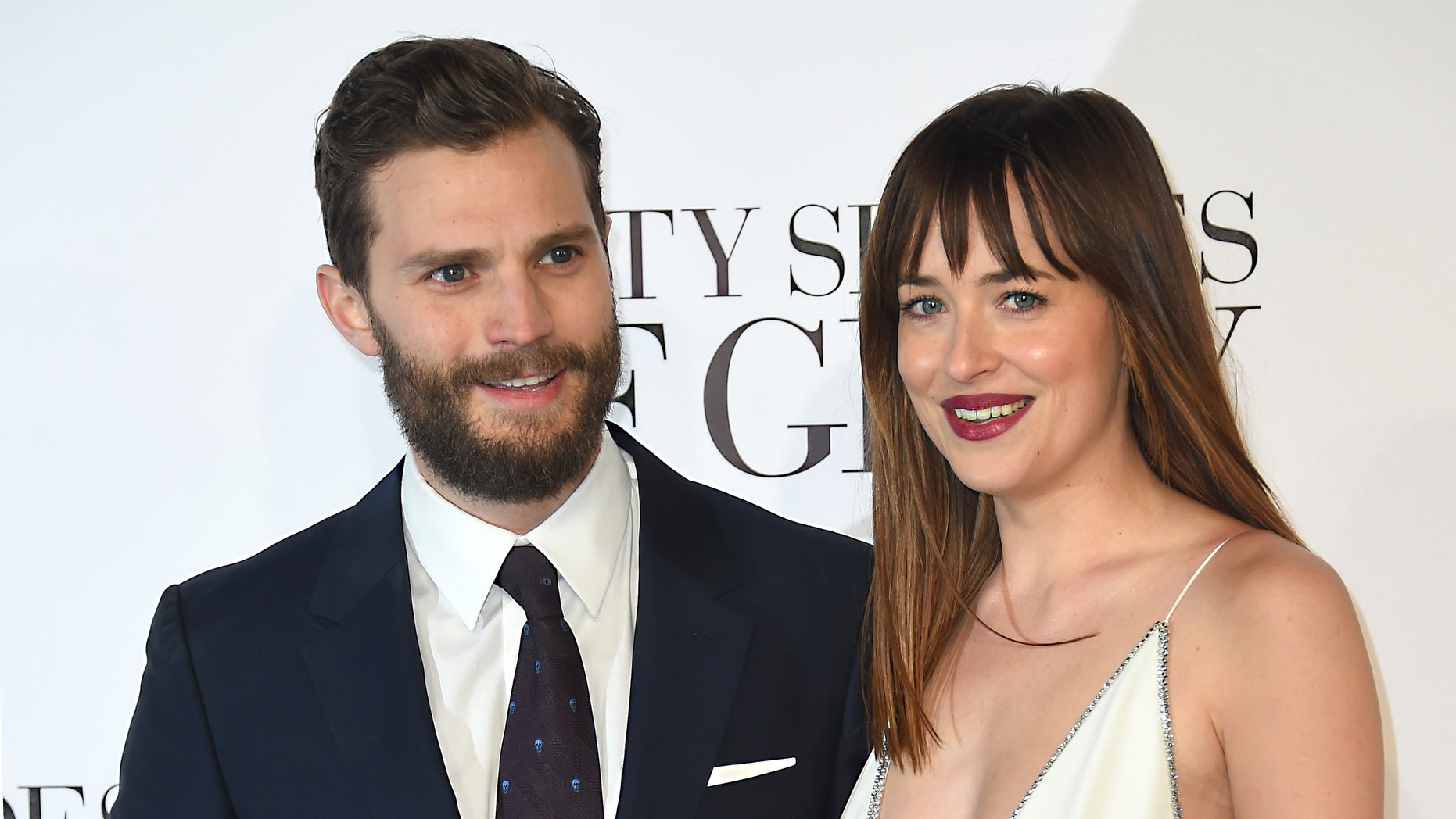 """Feb 12, 2015. Dakota Johnson, right, and Jamie Dornan pose for photographers at the UK Premiere of  """"Fifty Shades of Grey"""" in London."""
