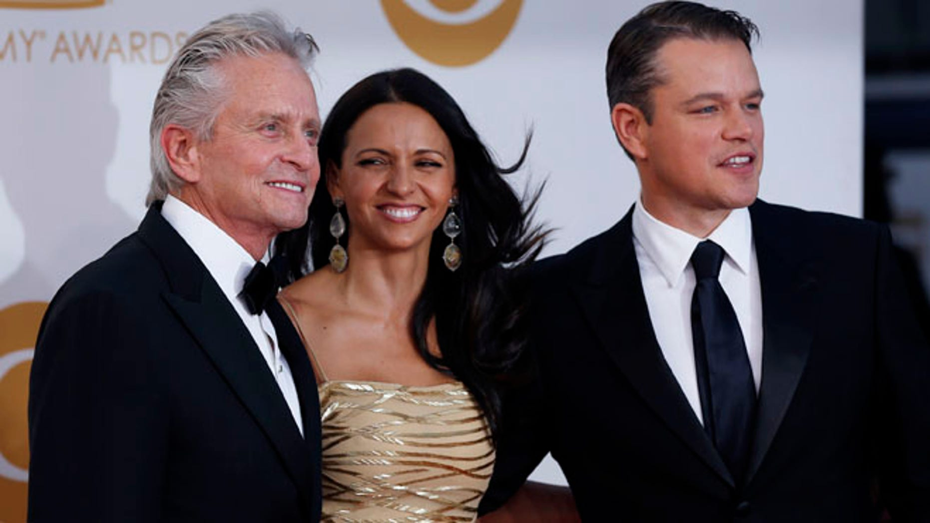 """Actor Michael Douglas from HBO's movie """"Behind the Candelabra"""" arrives with co-star Matt Damon and his wife, Luciana Barroso, at the 65th Primetime Emmy Awards in Los Angeles September 22, 2013. REUTERS/Mario Anzuoni (UNITED STATES Tags: ENTERTAINMENT) (EMMYS-ARRIVALS) - RTX13VT2"""