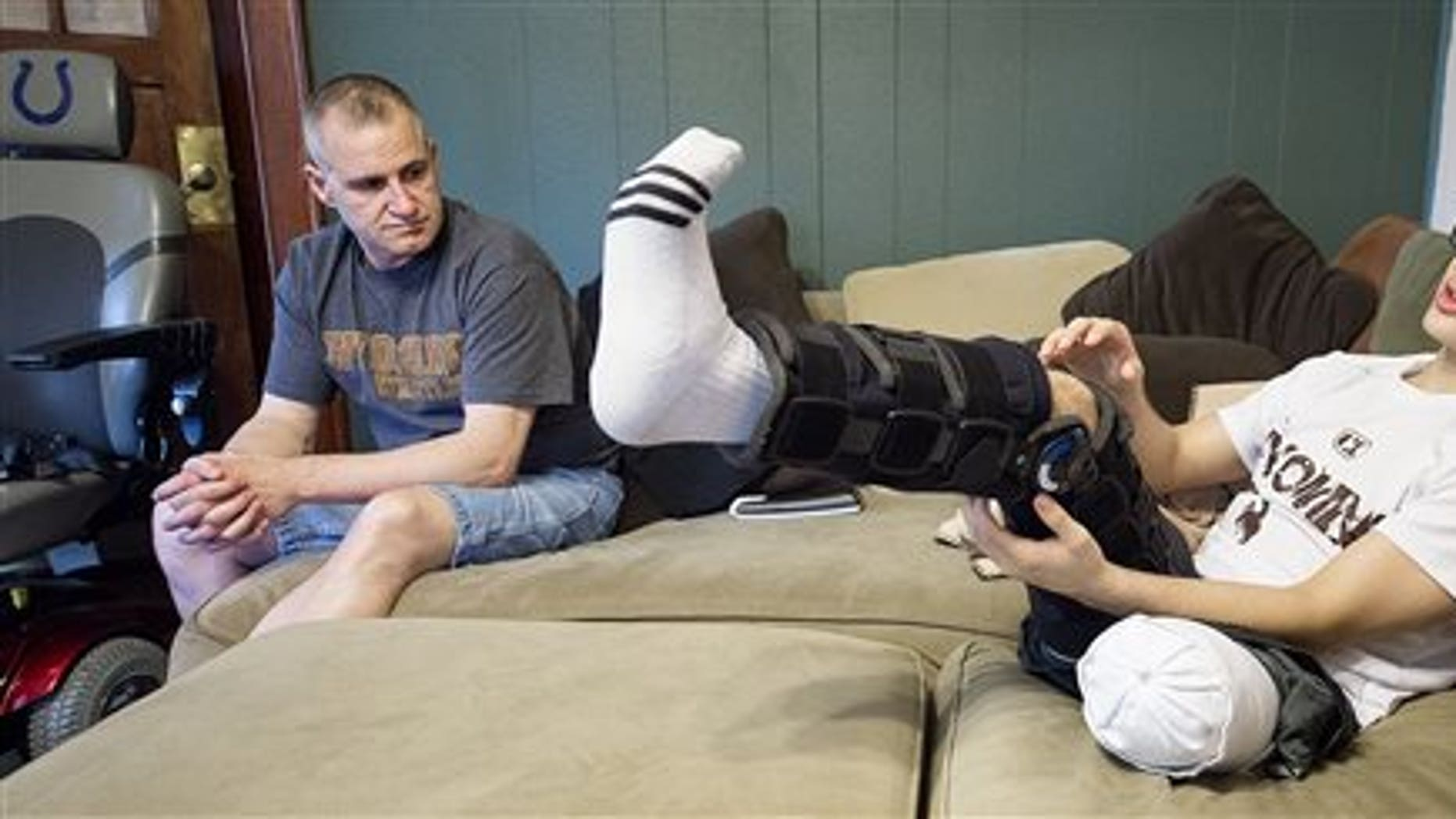 Centennial High School senior Doyle Trout, right, plays with his leg during an interview with his father Jon Trout in the living room of the family's home in Waco, Neb. on Saturday, May 16, 2015.(Francis Gardler/The Journal-Star via AP)