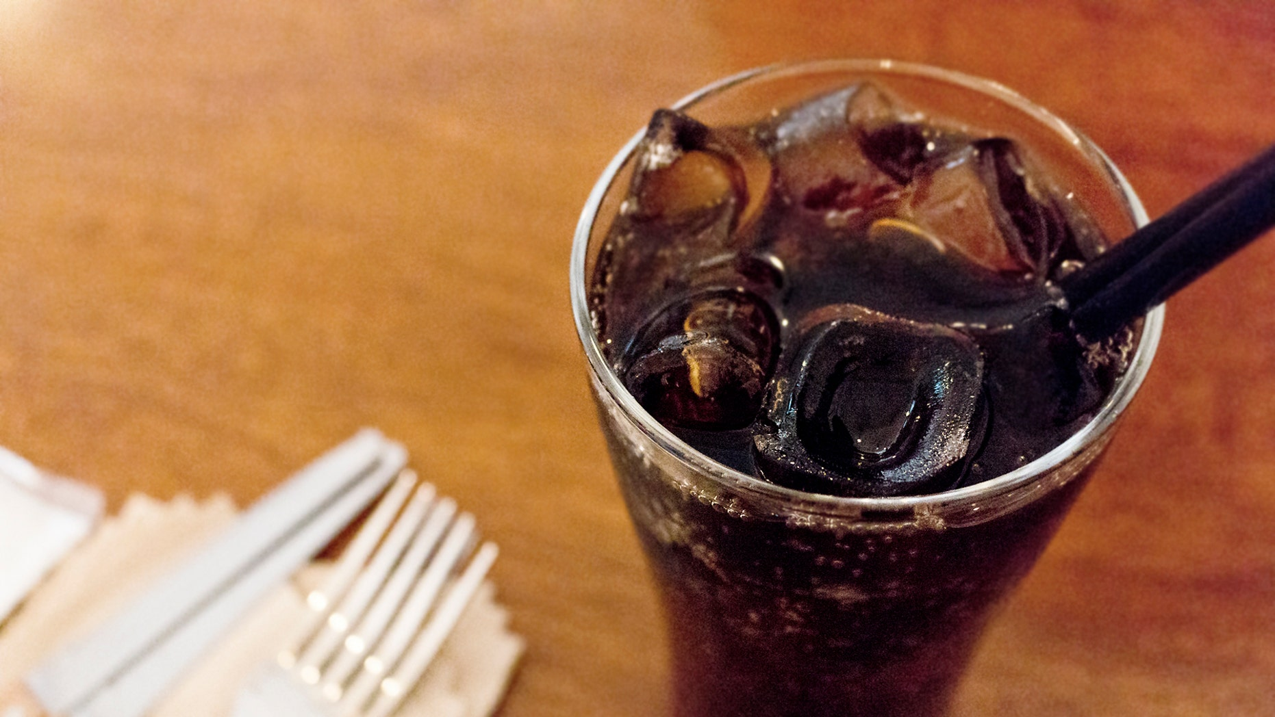 Glass of cold soda on wood table. with straw. napkin, forks and knives