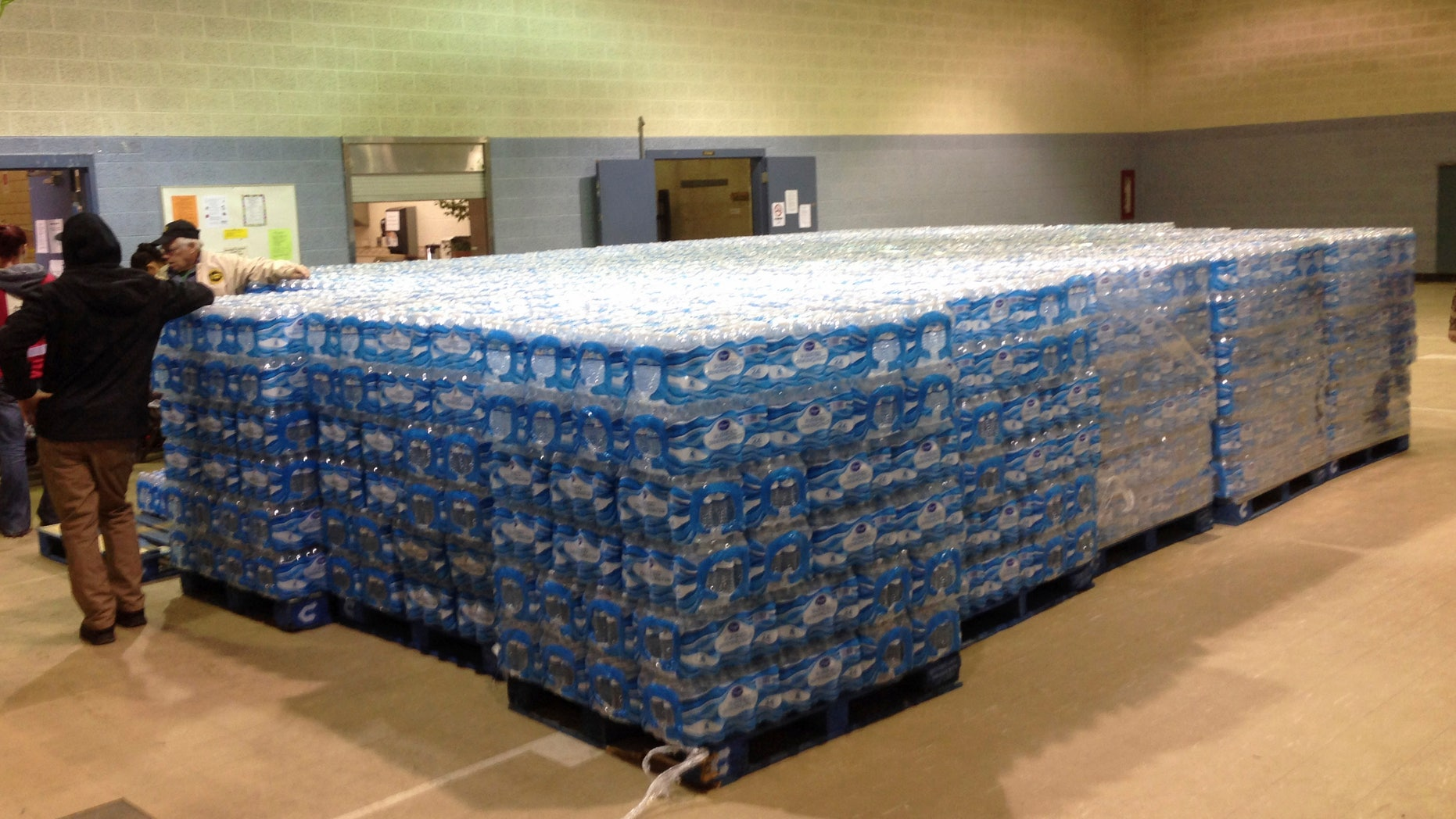 Pallets of water, ready for distribution in the community, sit at the Sebring Community Center, Tuesday, Jan. 26, 2016 in Sebring, Ohio. Authorities have been handing out bottled water, and schools were closed Tuesday for a third day in Sebring, a village about 60 miles southeast of Cleveland. The Sebring water system serves 8,100 homes and businesses in three Mahoning County communities. Testing over the weekend in Sebring found one school drinking fountain with lead levels that exceed EPA standards. (AP Photo/Mark Gillispie)