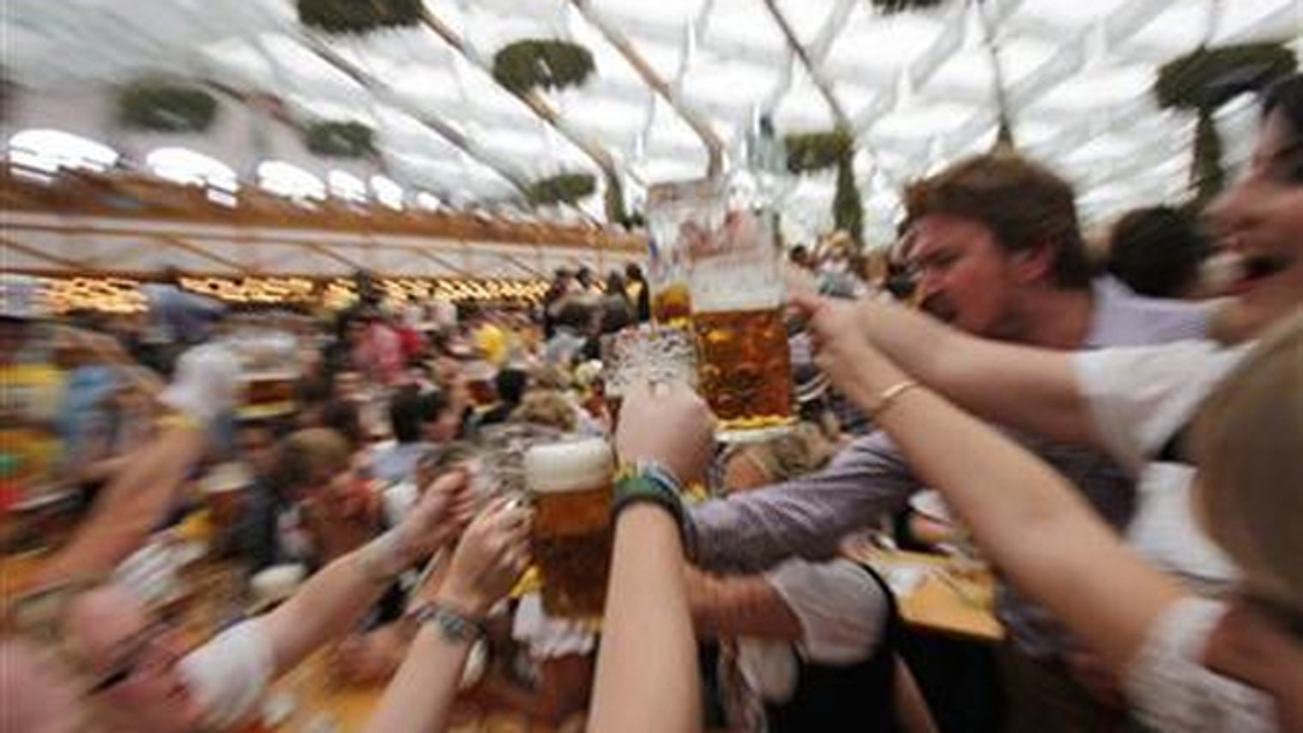 People wearing traditional Bavarian clothes toast with beer during the opening day of the 177th Oktoberfest in Munich September 18, 2010.
