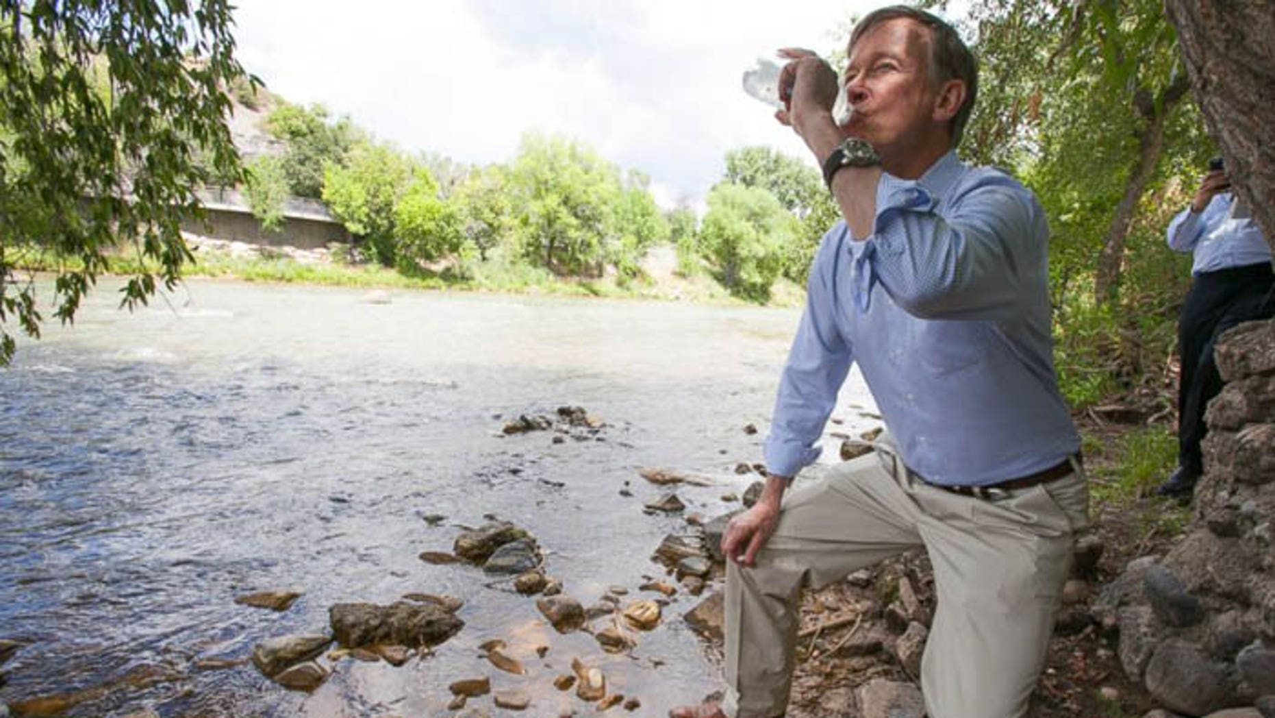 Colorado Gov. John Hickenlooper drank water straight from the contaminated river to prove a point, but critics said he proved he's crazy. (AP via Durango Herald)