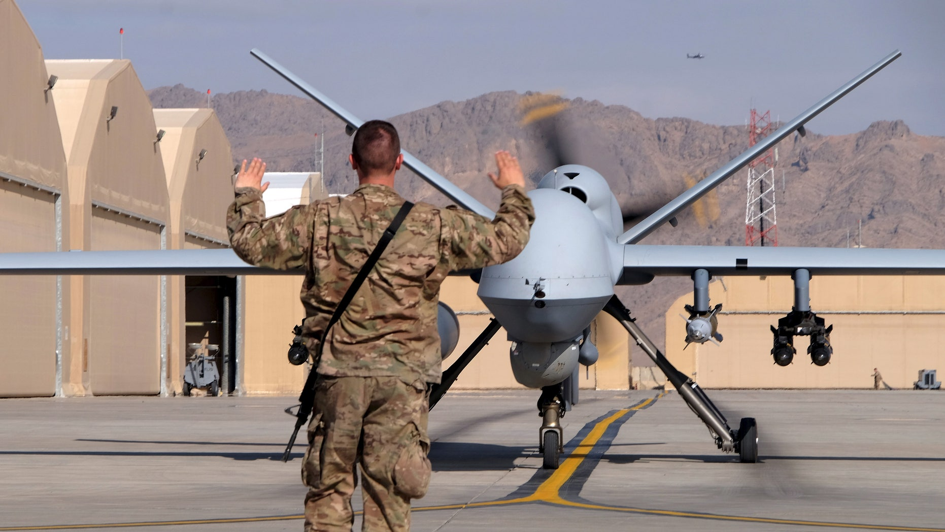 A U.S. airman guides an MQ-9 Reaper drone as it taxis to the runway at Kandahar Airfield, Afghanistan, in March.