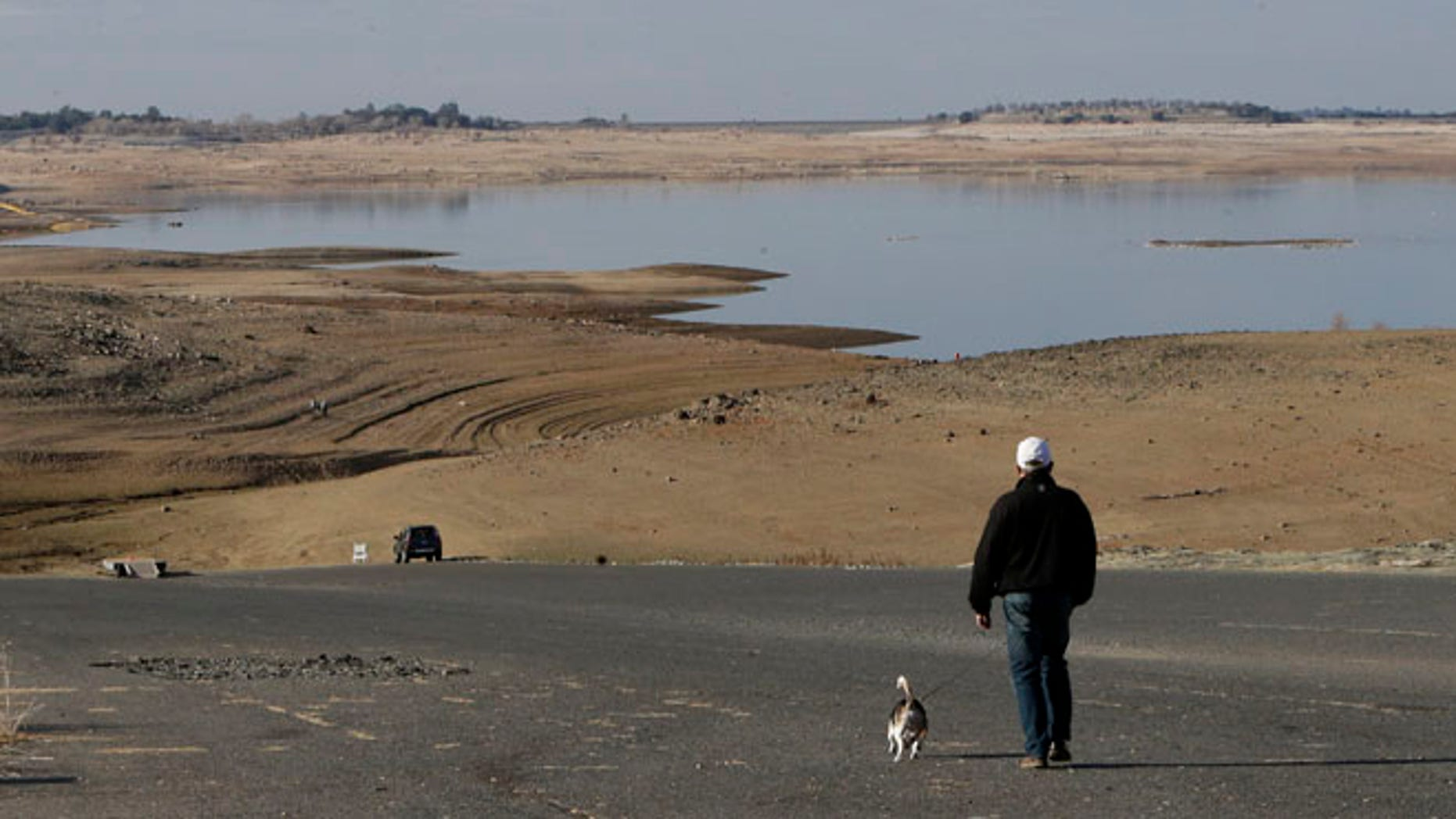 Jan. 9, 2014: In this file photo a visitor to Folsom Lake, Calif.,  walks his dog down a boat ramp that is now several hundred yards away from the waters edge, in Folsom, Calif.
