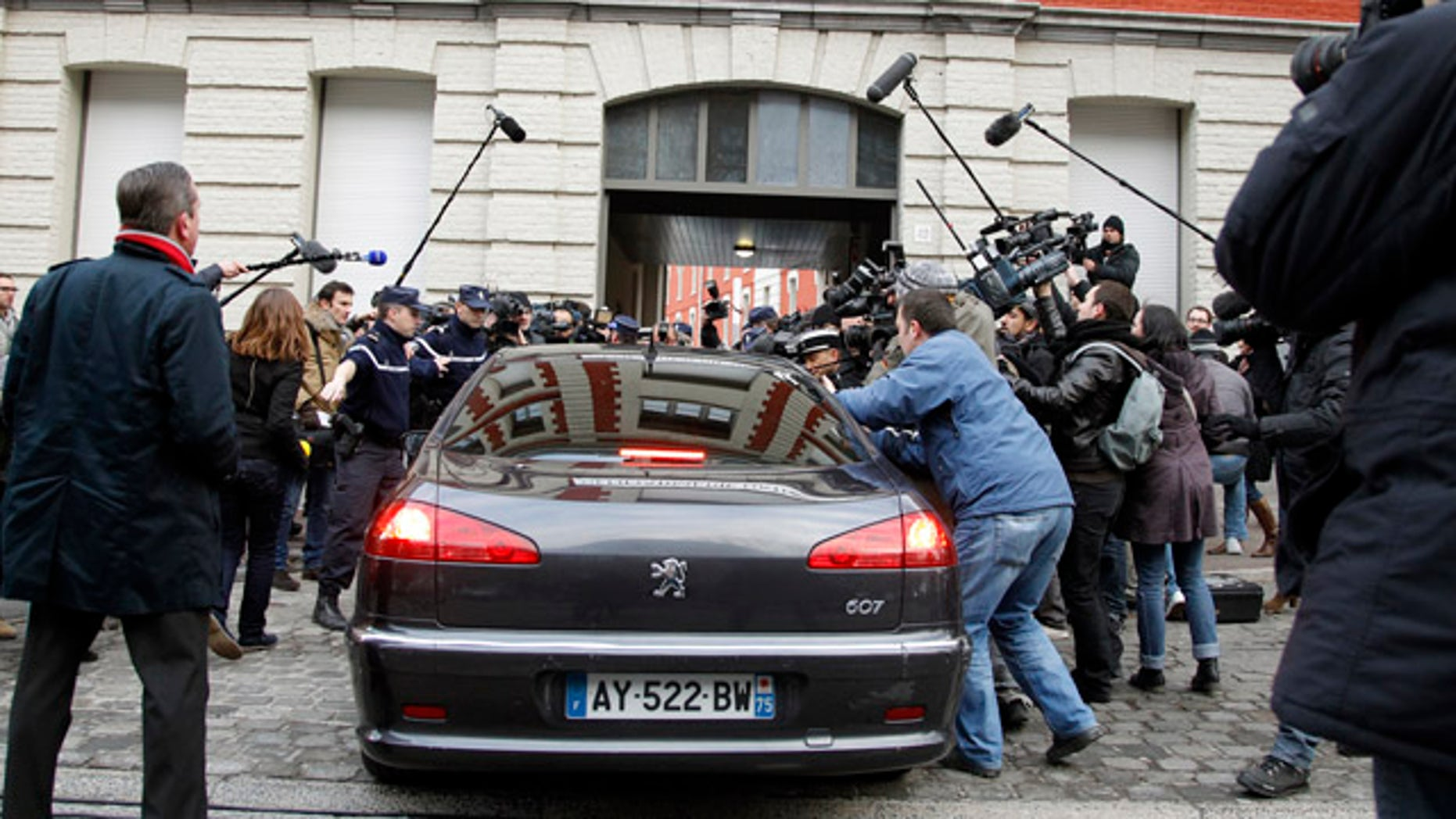Feb. 21: The car of Dominique Strauss-Kahn enters the Gendarmerie surrounded by the media as he arrives for questioning.