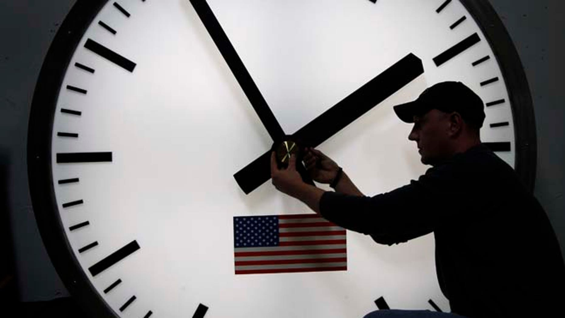A worker adjusts the hands on a stainless steel tower clock in Medfield, Mass., in this March 7, 2014 file photo.