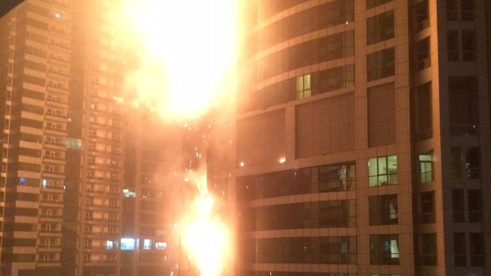 Feb. 21, 2015: This photo provided by Rhea Saran shows flames coming from a high rise tower in Dubai's marina district.