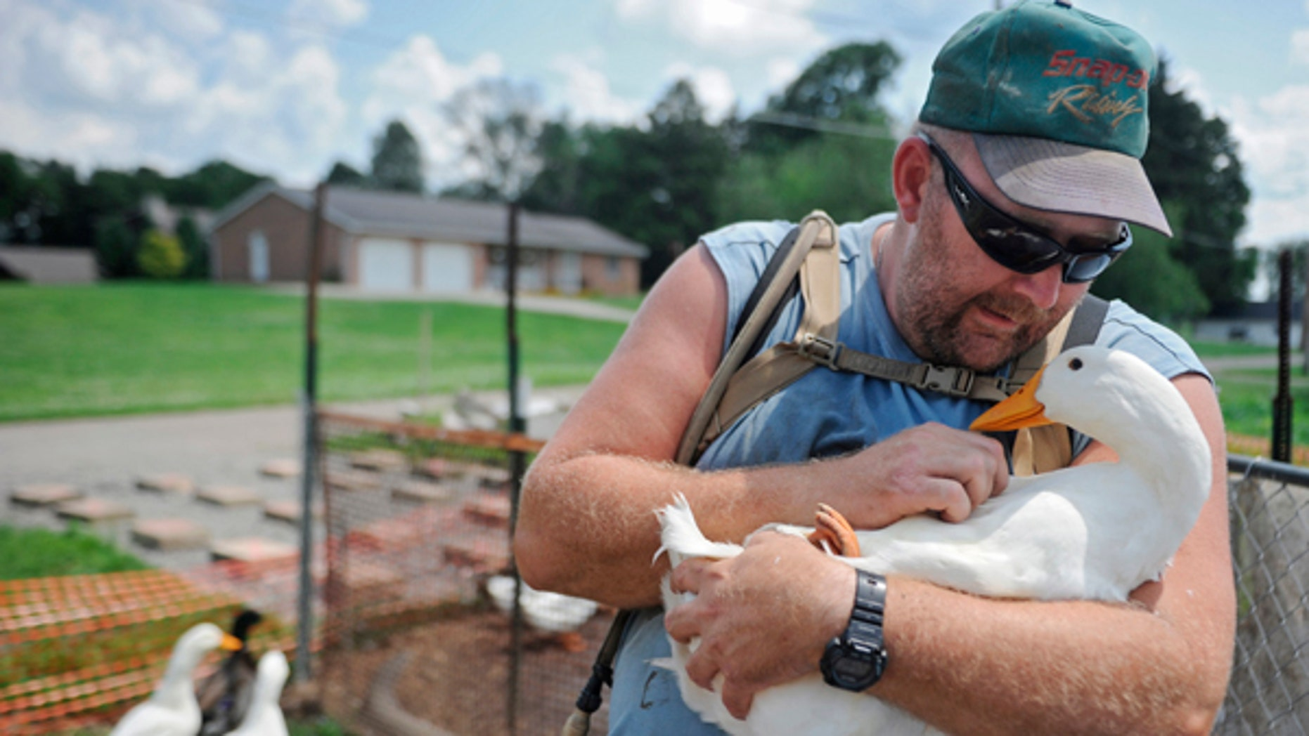 Iraq War veteran Darin Welker holds one of his ducks at his home in West Lafayette, Ohio. West Lafayette Village Council members voted Tuesday to grant a variance allowing Welker to keep pet ducks he says help relieve his post-traumatic stress disorder and depression.