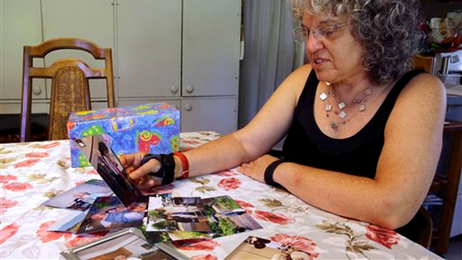 In this July 1, 2015 photo, Roslyn Duffy looks through photos of her late mother, Evelyn Nappa, at her home in Seattle. Duffy had to scramble to find a home willing to take Medicaid payments after her mother was evicted from a Seattle assisted-living facility. The stress and the change of surroundings strained her mother's health, Duffy said, and six weeks after moving, she was dead. (AP Photo/Ted S. Warren)