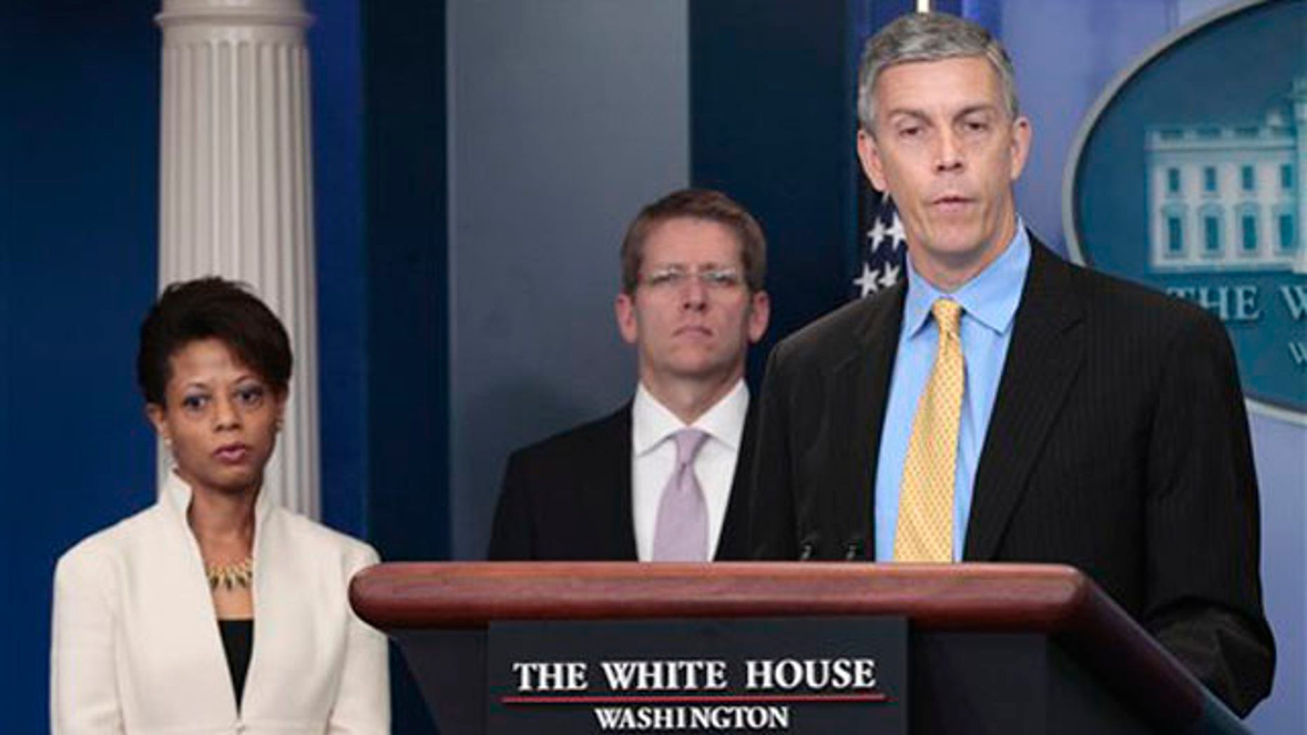 Education Secretary Arne Duncan, right, accompanied by White House Press Secretary Jay Carney, center, and Domestic Policy Council Director Melody Barnes, speaks at the White House in Washington Aug. 8.