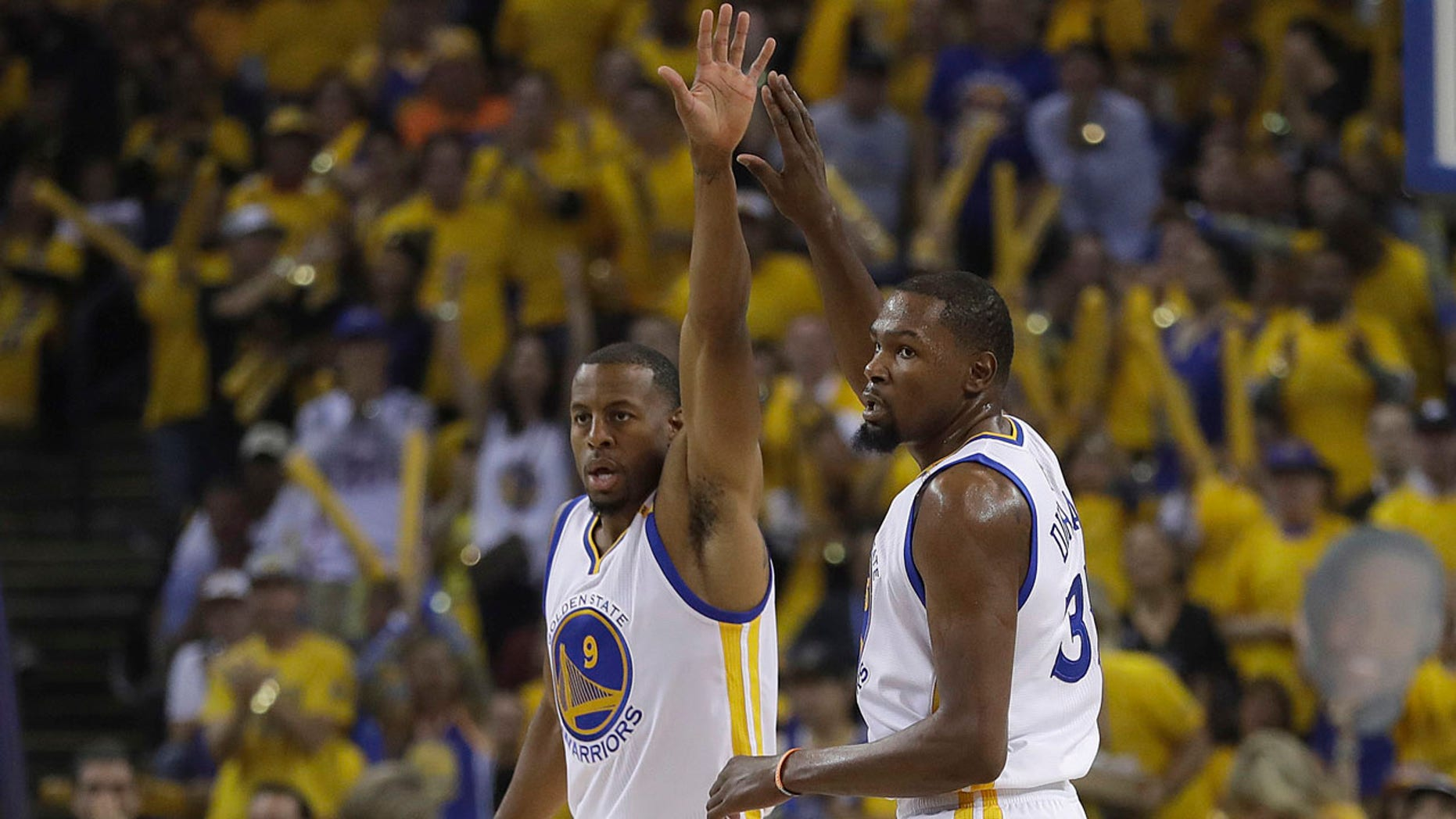 Golden State Warriors forward Andre Iguodala (9) and forward Kevin Durant (35) react after scoring against the Cleveland Cavaliers during the first half of Game 1 of basketball's NBA Finals in Oakland, Calif., Thursday, June 1, 2017. (AP Photo/Marcio Jose Sanchez)