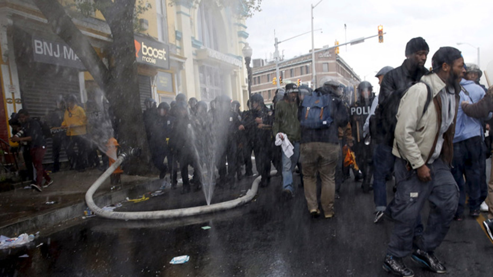 APRIL 2015: A fire hose cut by rioters sprays water into the air as protesters and a line of police move in at the site of a burning CVS drug store during clashes in Baltimore