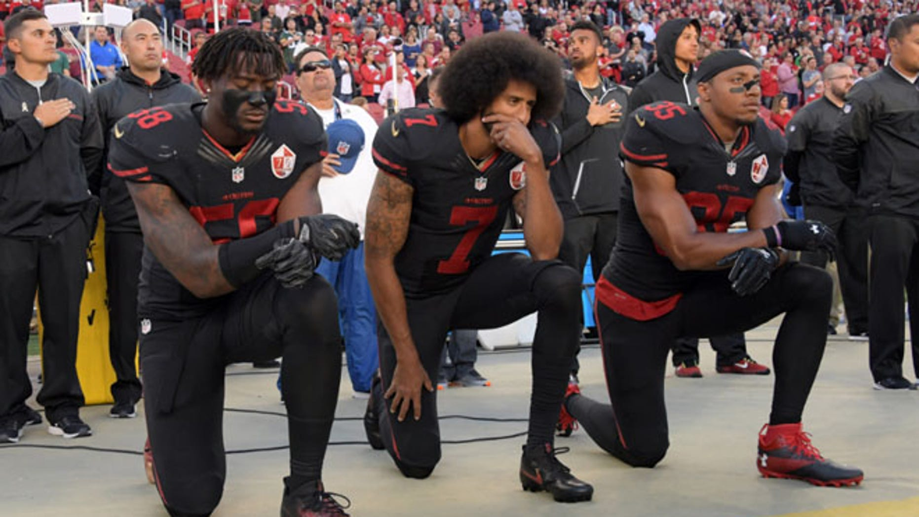 FILE 2016: San Francisco 49ers outside linebacker Eli Harold (58), quarterback Colin Kaepernick (7) and free safety Eric Reid (35) kneel in protest.
