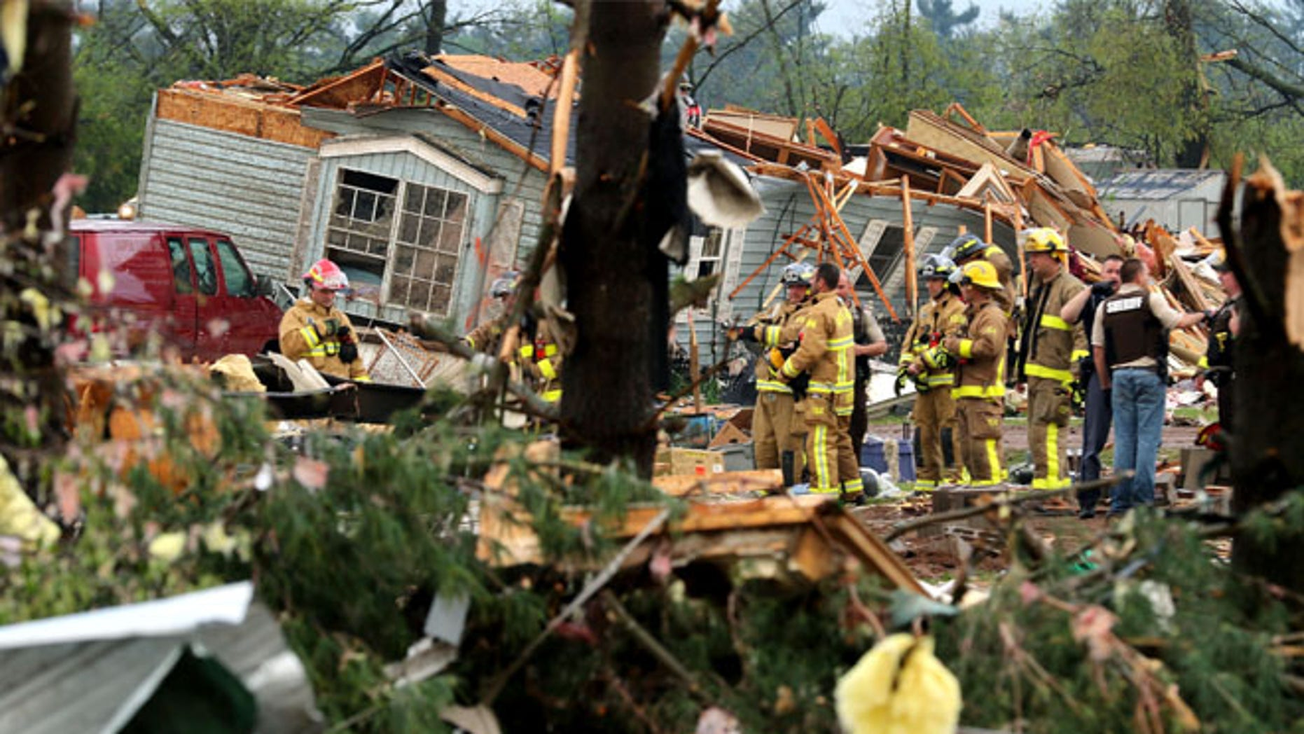 Firefighters work the site of the damage after a tornado ripped through Prairie Lake Estates trailer home park, just north of Chetek, Wis