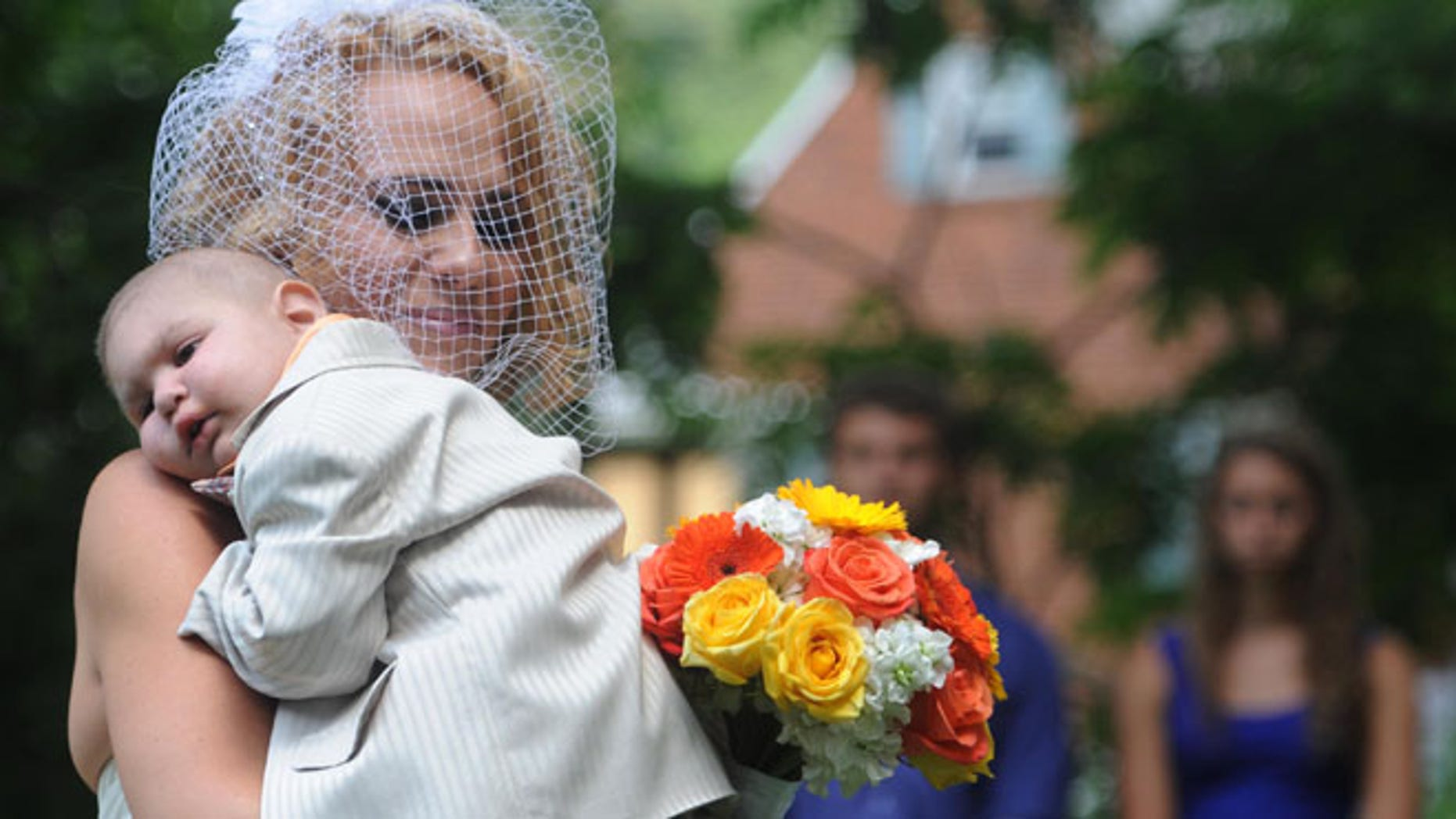 Aug. 3: Christine Swidorsky carries her son and the couple's best man, Logan Stevenson, down the aisle during the wedding ceremony in Jeannette, Pa.