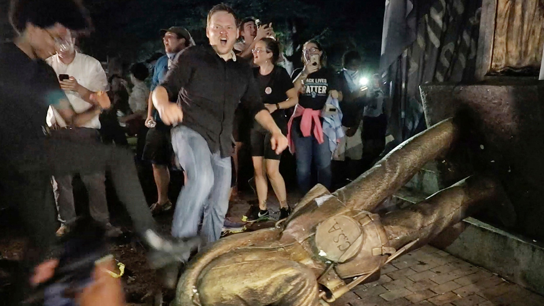 """Aug. 20: Protesters celebrate after the Confederate statue known as """"Silent Sam"""" was toppled on the campus of the University of North Carolina in Chapel Hill."""