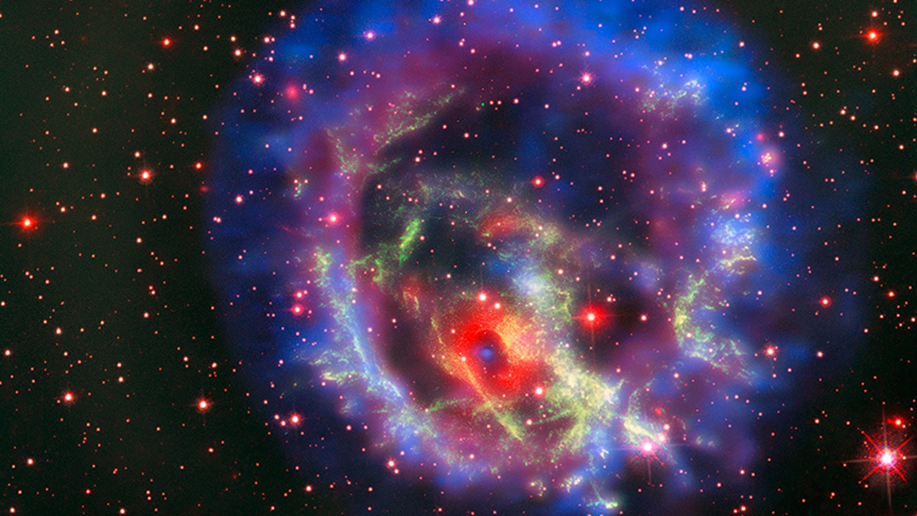 The new composite image of neutron star E0102, released on May 23, combines data from NASA's Chandra X-Ray Observatory (seen in blue and purple), the Multi Unit Spectroscopic Explorer instrument on the European Southern Observatory's Very Large Telescope in Chile (in bright red) and the Hubble Space Telescope (in dark red and green).