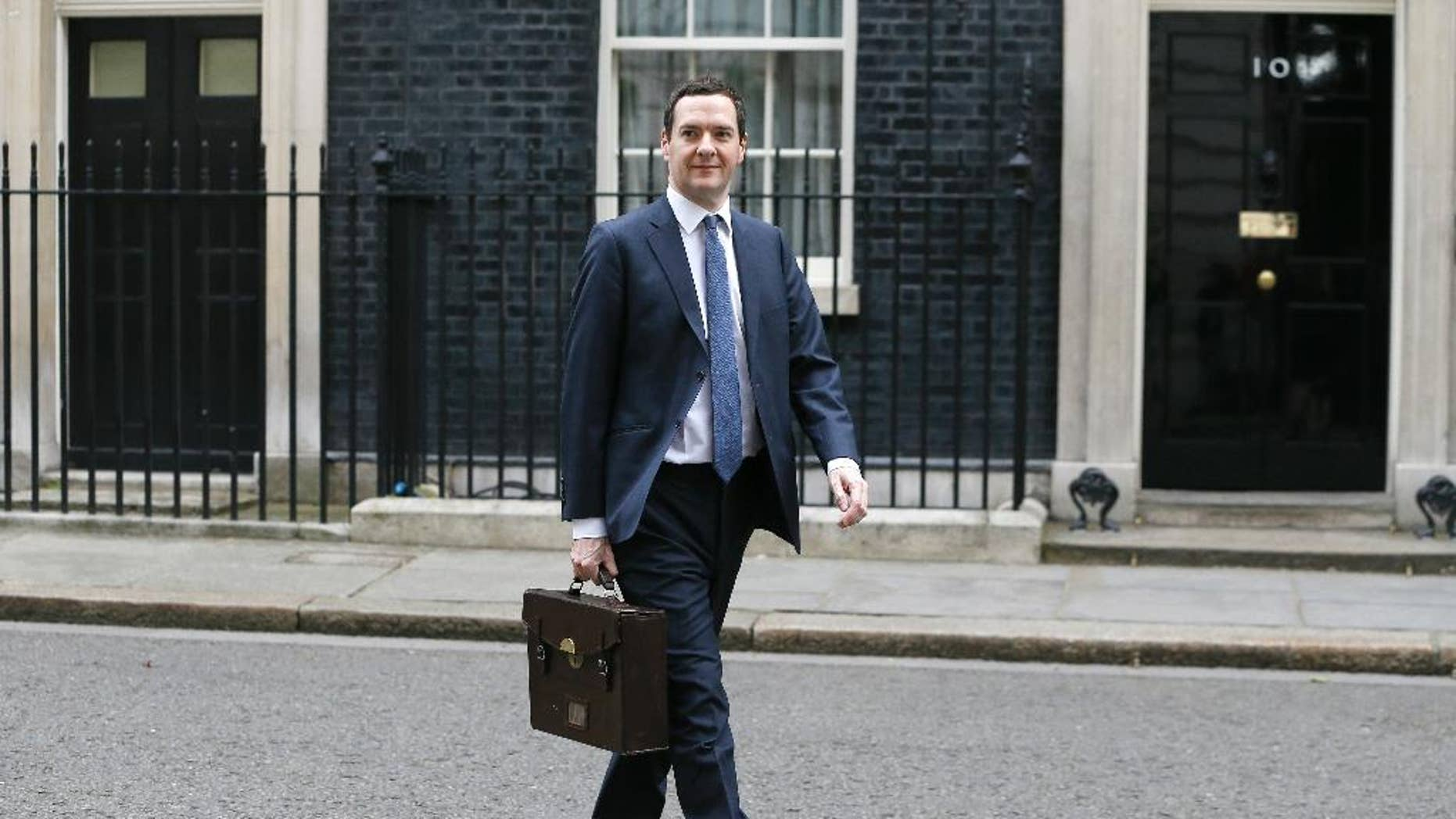 """Britain's Chancellor George Osborne walks across Downing Street on his way to attend a press conference at the Foreign Office with Christine Lagarde of the International Monetary Fund, in London, Friday, May 13, 2016. The International Monetary Fund has warned that London's status as a global financial center would be jeopardized should Britain vote to leave the European Union in a June 23 referendum. The global body that promotes financial stability says in a report Friday that the city's powerful financial services sector would lose clout because of the loss of so-called """"passporting'' rights. These rights allow professionals to work in any EU country, without seeking licenses. (AP Photo/Kirsty Wigglesworth)"""
