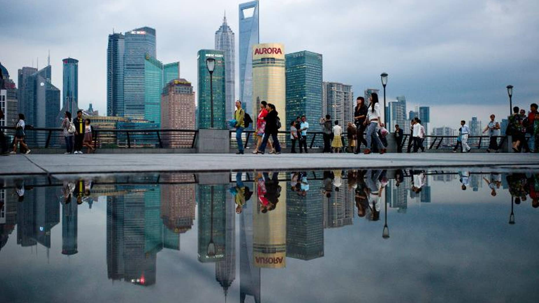 Pedestrians walk past the skyline of the city's financial district in Shanghai on October 8, 2010.