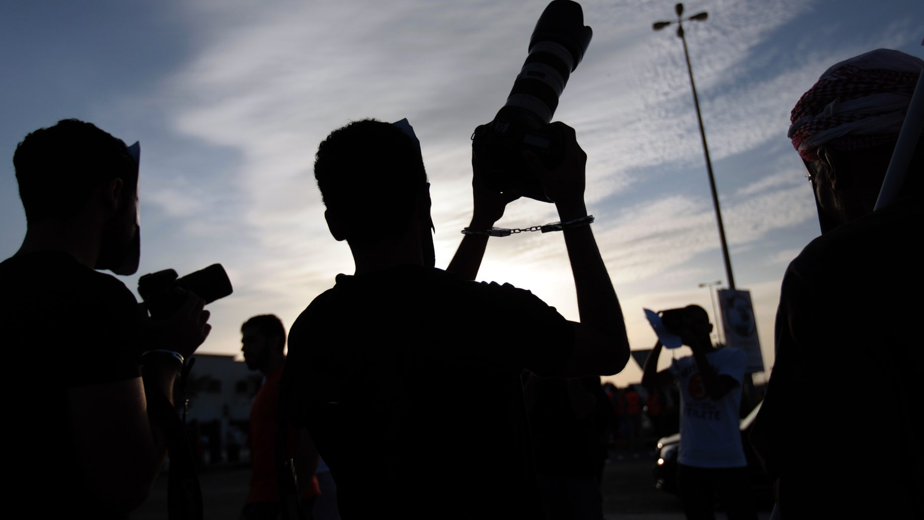 Masked Bahraini anti-government protesters wearing handcuffs hold cameras up to show support for jailed photographers during a march in Saar, Bahrain, on Friday, Dec. 13, 2013. Thousands participated in the march organized by opposition parties to mark 1,000 days since the pro-democracy uprising began in the Gulf island kingdom. As the peaceful march dispersed, a group of masked youths confronted riot police nearby, igniting clashes. (AP Photo/Hasan Jamali)