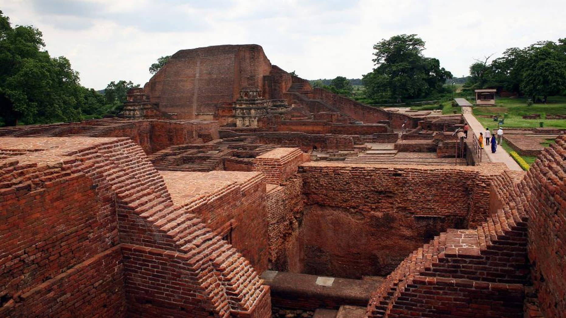 FILE � In this July 5, 2006 file photo, tourists walk at the ruins of the Nalanda University at Nalanda, India. UNESCO has put four new sites on its World Heritage List, including the archaeological site of Nalanda Mahavihara, or Nalanda University, on Friday, July 15, 2016. (AP Photo/Prashant Ravi, File)