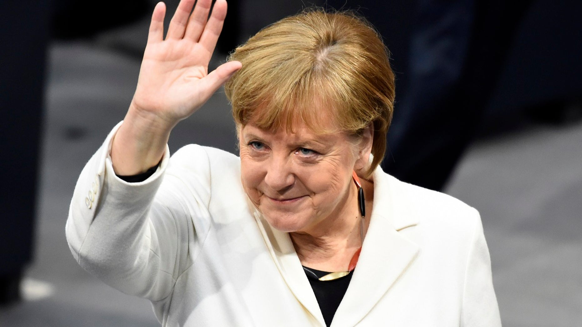 German Chancellor Angela Merkel waves when Germany's parliament Bundestag meets to elect Angela Merkel for a fourth term as chancellor in Berlin, Germany, Wednesday, March 14, 2018. (Gregor Fischer/dpa via AP)