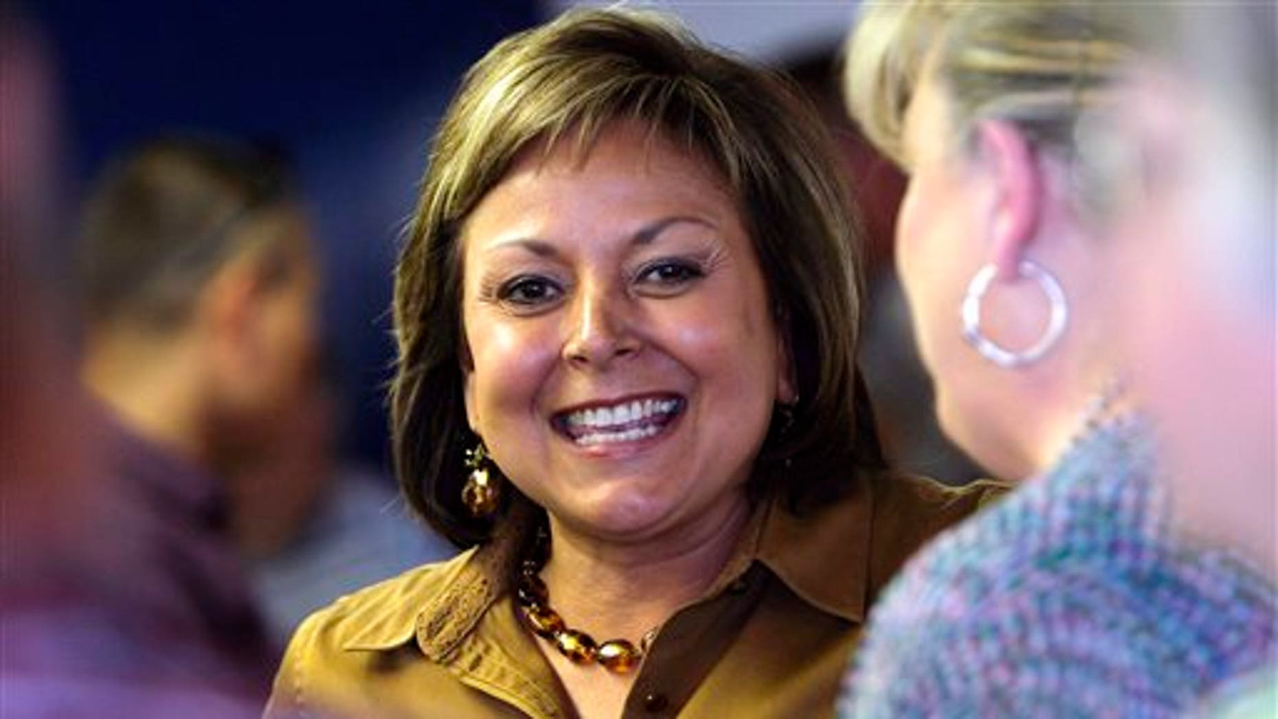 FILE - In this June 4, 2014 file photo, New Mexico Gov. Susana Martinez meets with supporters during a campaign stop at the San Juan County Republican Party Headquarters in Farmington N.M.  Democrat Gary King hopes to follow his fathers footsteps into the governorship of New Mexico but hes struggled to raise money and make headway against Republican Martinez, the nations only Latina governor. (AP Photo/The Daily Times, Jon Austria, File)