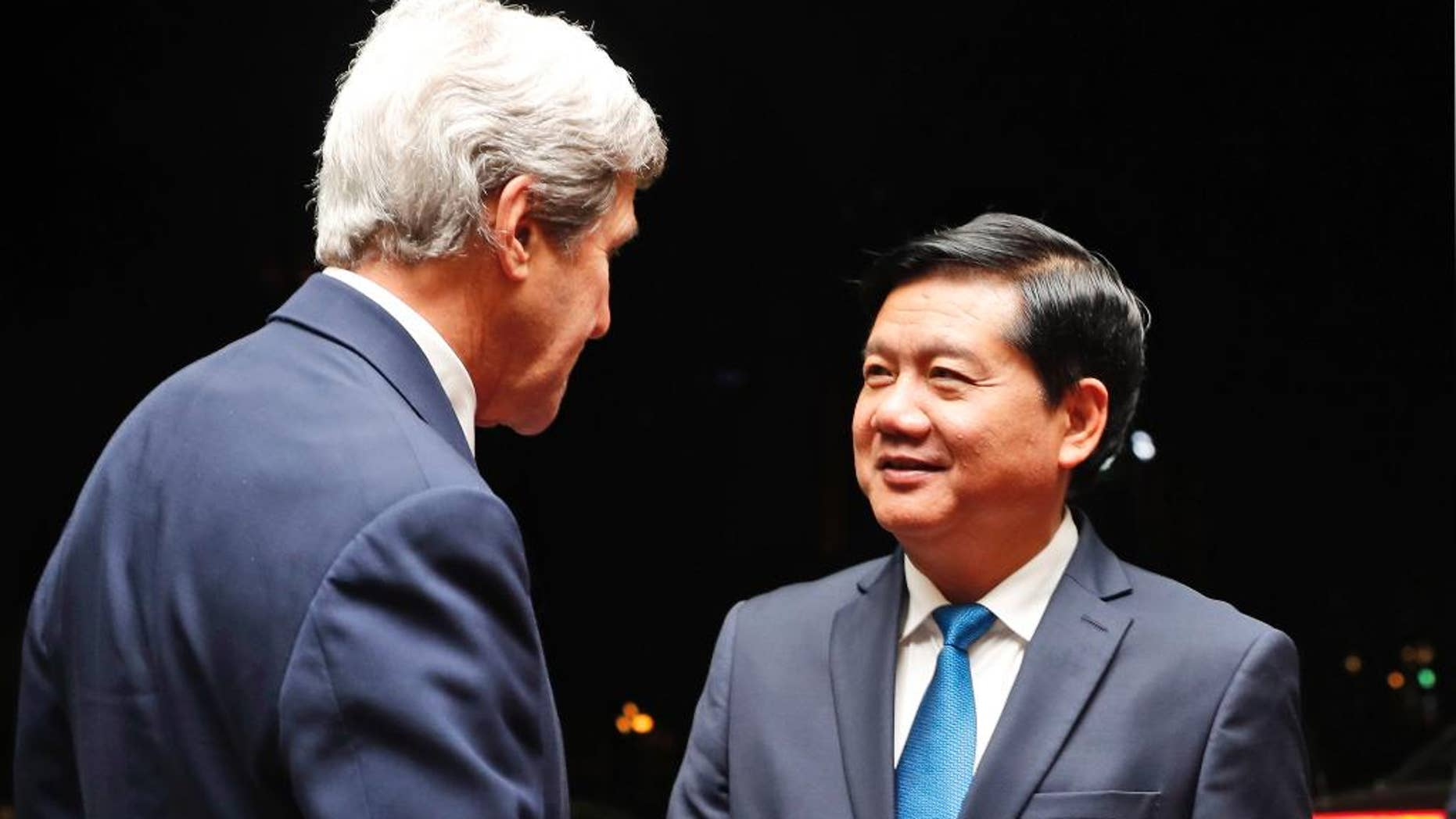 """FILE - In this Jan. 13, 2017 file photo, Ho Chi Minh City Party Committee Secretary Dinh La Thang, right, greets U.S. Secretary of State John Kerry upon Kerry's arrival for a meeting in Ho Chi Minh City, Vietnam. Thang has been removed from the powerful Politburo for committing """"very serious mistakes and violations"""" when he was head of the country's oil and gas monopoly PetroVietnam. The Central Committee voted in majority to impose the disciplinary measures against Thang, was chairman of the board of PetroVietnam from 2005 until he was appointed transport minister in 2011, according to a statement posted on the party's website late Sunday, May 7. (AP Photo/Alex Brandon, Pool, File)"""