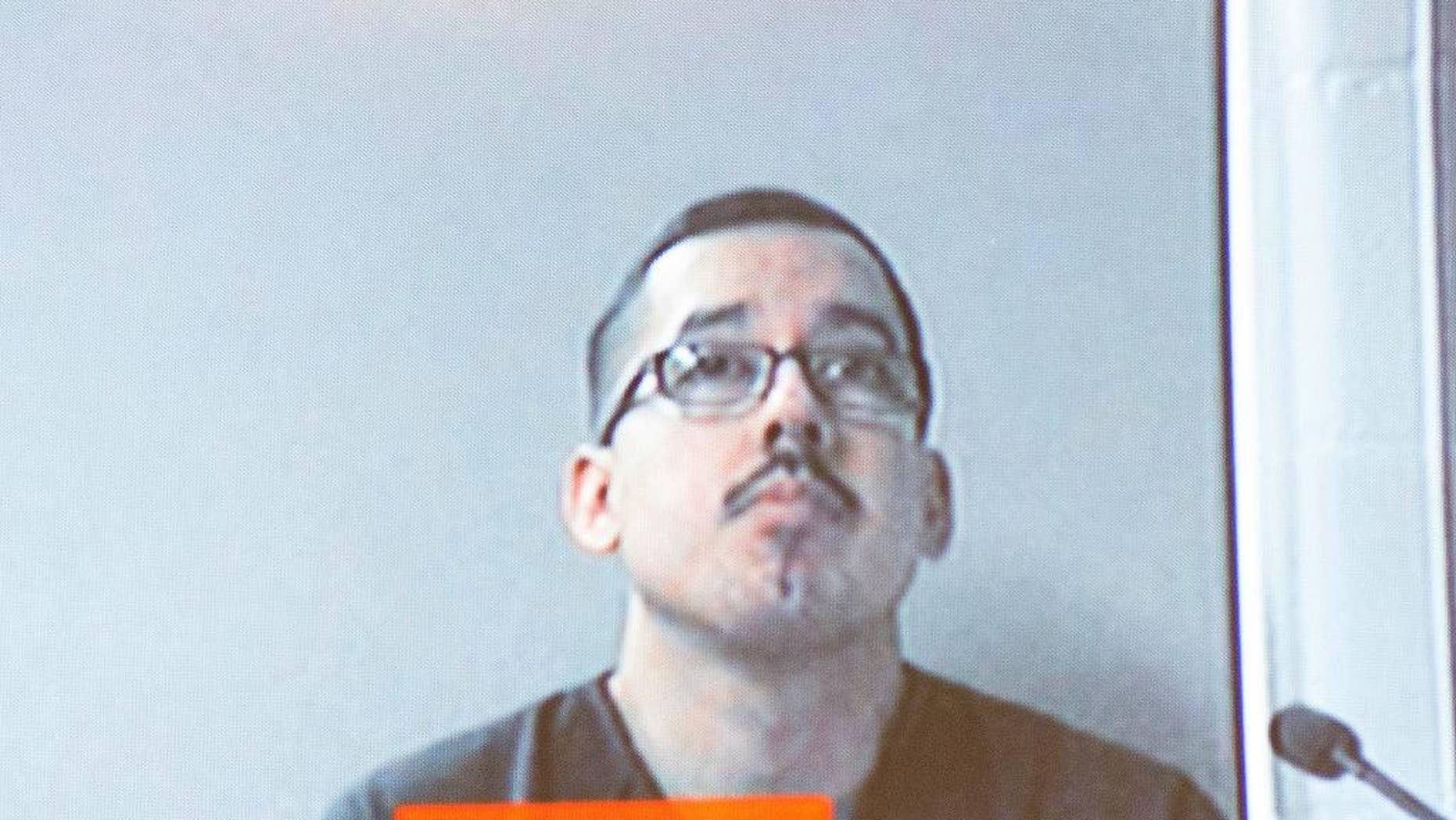 In this Dec. 7, 2016 photo, Ruben Hernandez, an FBI agent, appears via video screen from Kent County Jail as he's arraigned before Judge Michael Distel at the Kent County Courthouse in Grand Rapids, Mich. Hernandez was arrested in western Michigan for firing his gun at a police officer outside a fitness club on Tuesday, Dec. 6 and was arraigned Wednesday on charges including assault. (Kent County Courthouse/MLive.com-The Grand Rapids Press via AP)