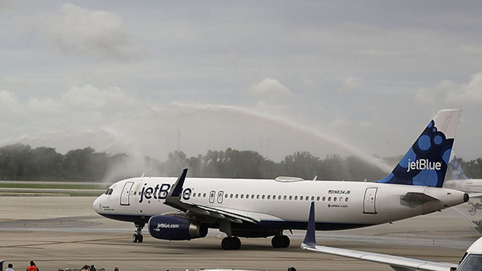 FORT LAUDERDALE, FL - AUGUST 31:  Workers watch as JetBlue Flight 387 is given a water cannon salute as it prepares for take off to become the first scheduled commercial flight to Cuba since 1961 on August 31, 2016 in Fort Lauderdale, Florida. JetBlue which hopes to have as many as 110 daily flights is the first U.S. airline to resume regularly scheduled airline service under new rules allowing Americans greater access to Cuba.  (Photo by Joe Raedle/Getty Images)