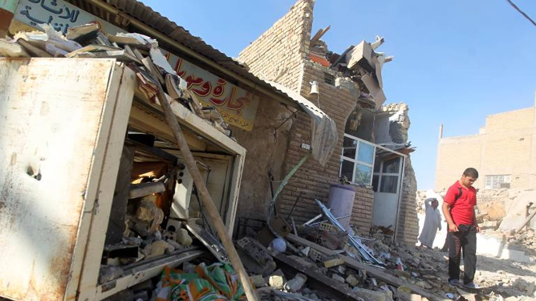 An Iraqi walks on the rubble of the Al-Hussein mosque following an explosion in the district of al-Musayyib, south of Baghdad, on September 30, 2013