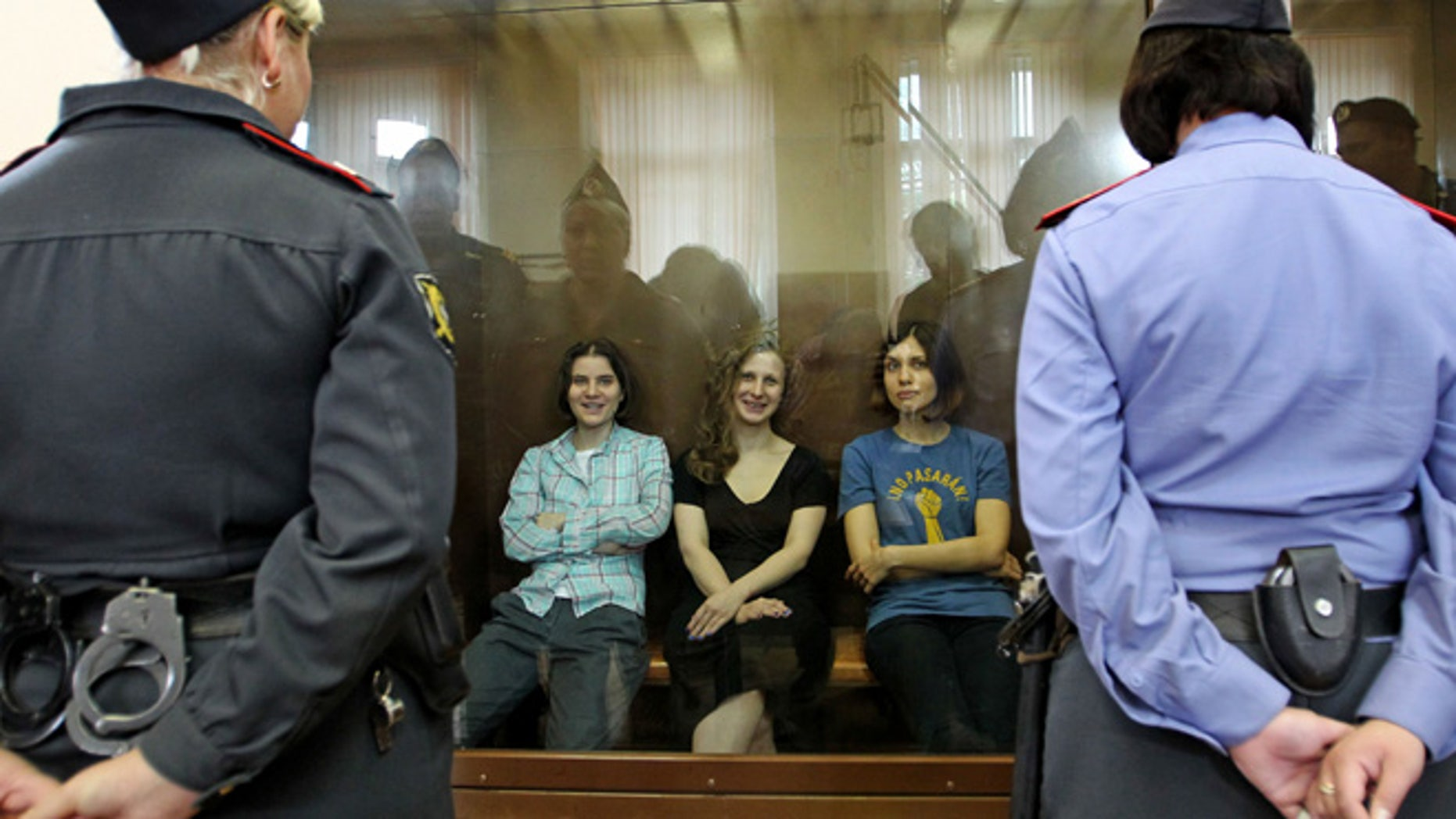 Aug. 17, 2012: Feminist punk group Pussy Riot members, from left, Yekaterina Samutsevich, Maria Alekhina and Nadezhda Tolokonnikova sit in a glass cage at a court room in Moscow, Russia .