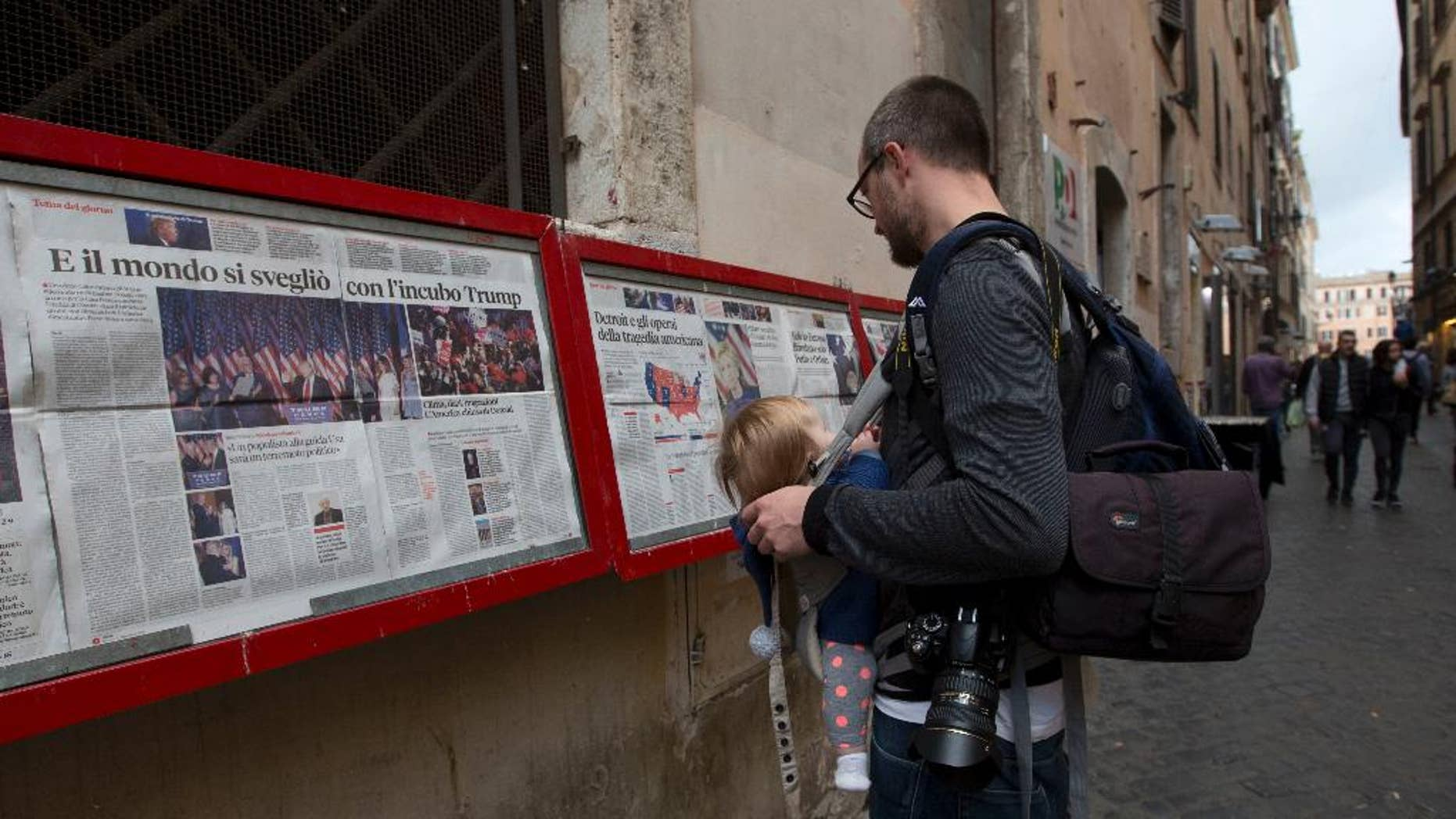 """Newspapers headlining the US President-elect Donald Trump's victory over Hillary Clinton hang from a wall outside a Democratic party office in downtown Rome, Thursday, Nov. 10, 2016. Headline reads in Italian """"And the world woke up with Trump nightmare"""". (AP Photo/Alessandra Tarantino)"""