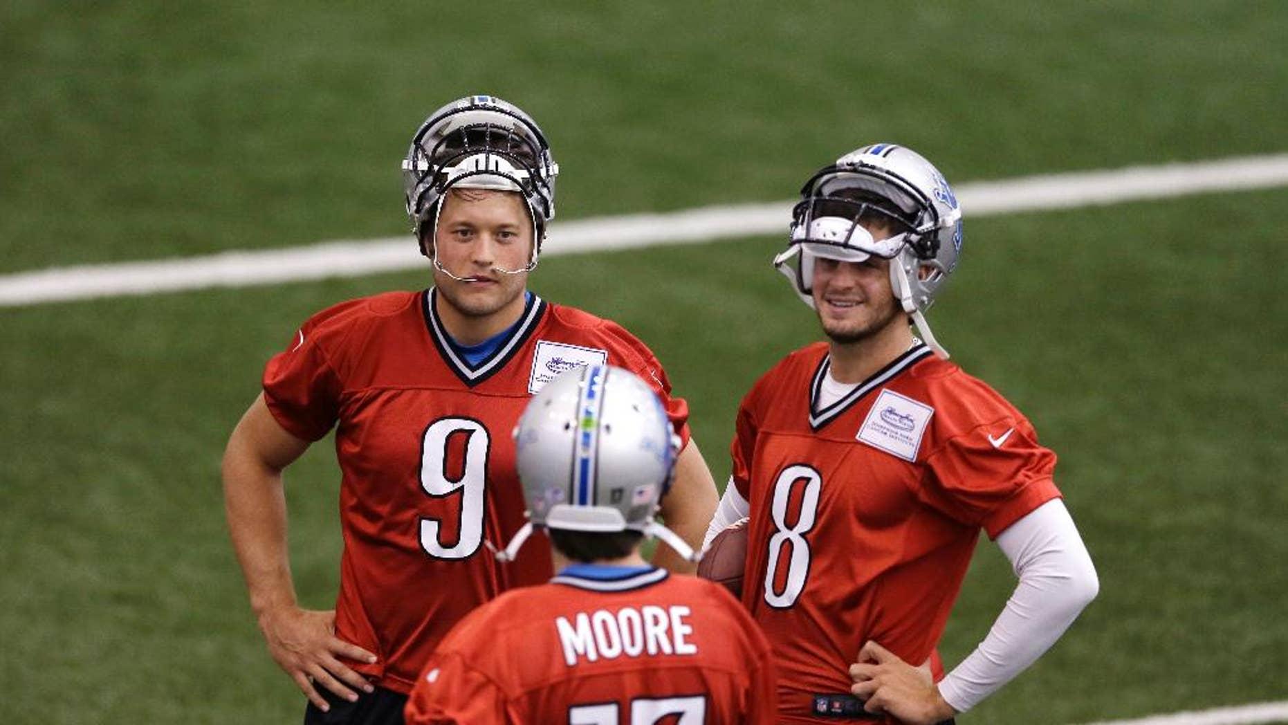 Detroit Lions quarterbacks Matthew Stafford (9) and Dan Orlovsky (8) talk with quarterback Kellen Moore (17) during an NFL football training camp, Monday, Aug. 11, 2014, in Allen Park, Mich. (AP Photo/Carlos Osorio)