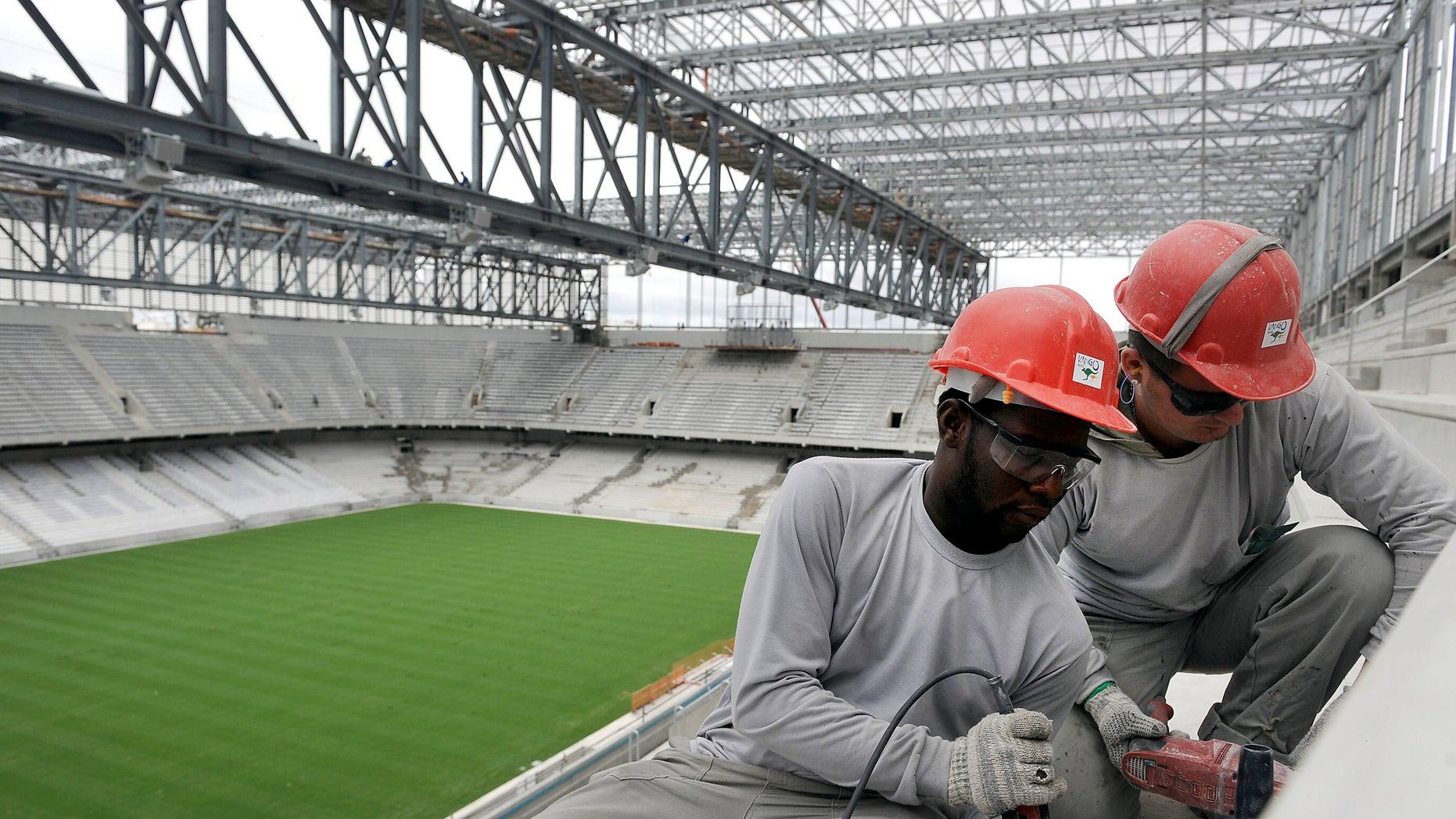 Personnel work on the construction of Arena da Baixada in Curitiba, Brazil, Tuesday, Feb. 18, 2014.