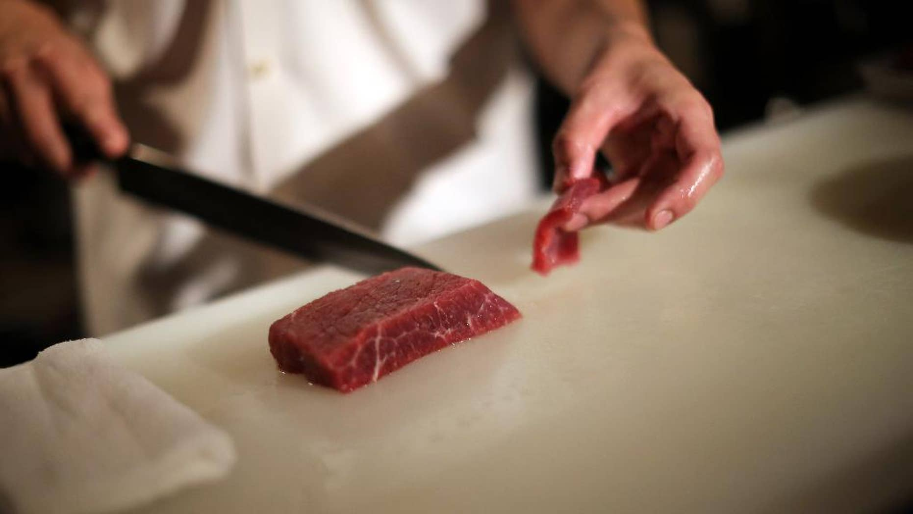 """In this Sept. 11, 2014 photo, chef of the Japanese restaurant """"COM FOR TABLE"""" slices whale meat for a dish in in Tokyo. Whale meat continues to be one of the favorite dishes in this restaurant, but restaurant manager concerns about the future of its supply. At the International Whaling Commission meeting in Slovenia which opens Monday, Sept. 15, 2014, Japan is expected to seek international support for its plans to hunt minke whales in the Antarctic Ocean next year by scaling down the whaling research program the U.N. top court rejected earlier this year. The restaurant manager is hoping that supply will continue to sustain the demand for whale meat which has been a staple for the Japanese for such a long time. (AP Photo/Eugene Hoshiko)"""