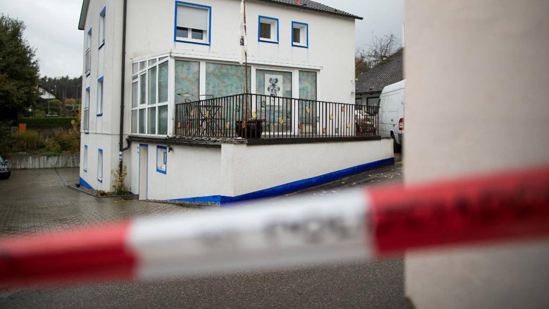 The house in which a 49-year-old anti-government extremist fired at four policemen during a raid on the Wednesday is pictured in Georgensgmuend, Germany, Thursday, Oct. 20, 2016. A 32-year-old police officer died early Thursday, a day after being shot by by the extremist who had hoarded dozens of weapons at his home, officials said. (Daniel Karmann/dpa via AP)