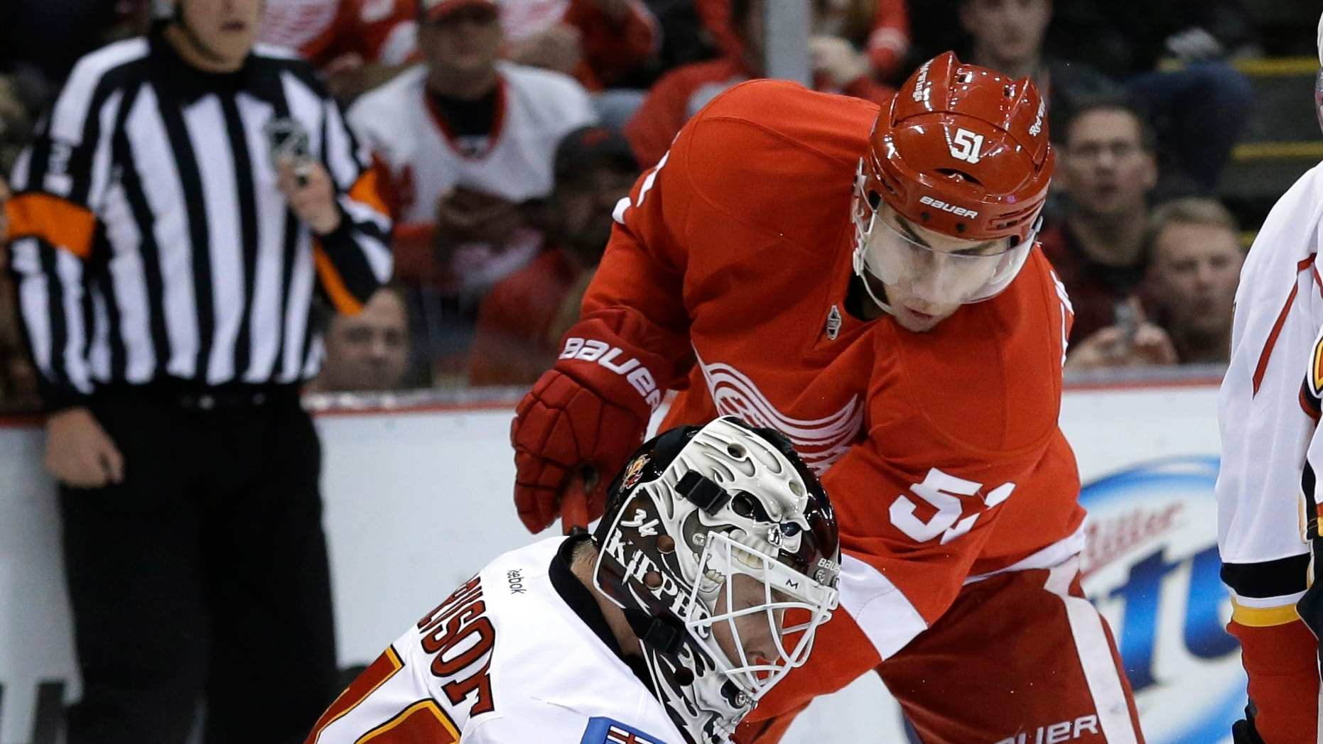 CORRECTS MONTH - Calgary Flames goalie Miikka Kiprusoff (34), of Finland, stops a shot by Detroit Red Wings center Valtteri Filppula (51), of Finland, during the first period of an NHL hockey game in Detroit, Tuesday, Feb. 5, 2013.  (AP Photo/Paul Sancya)