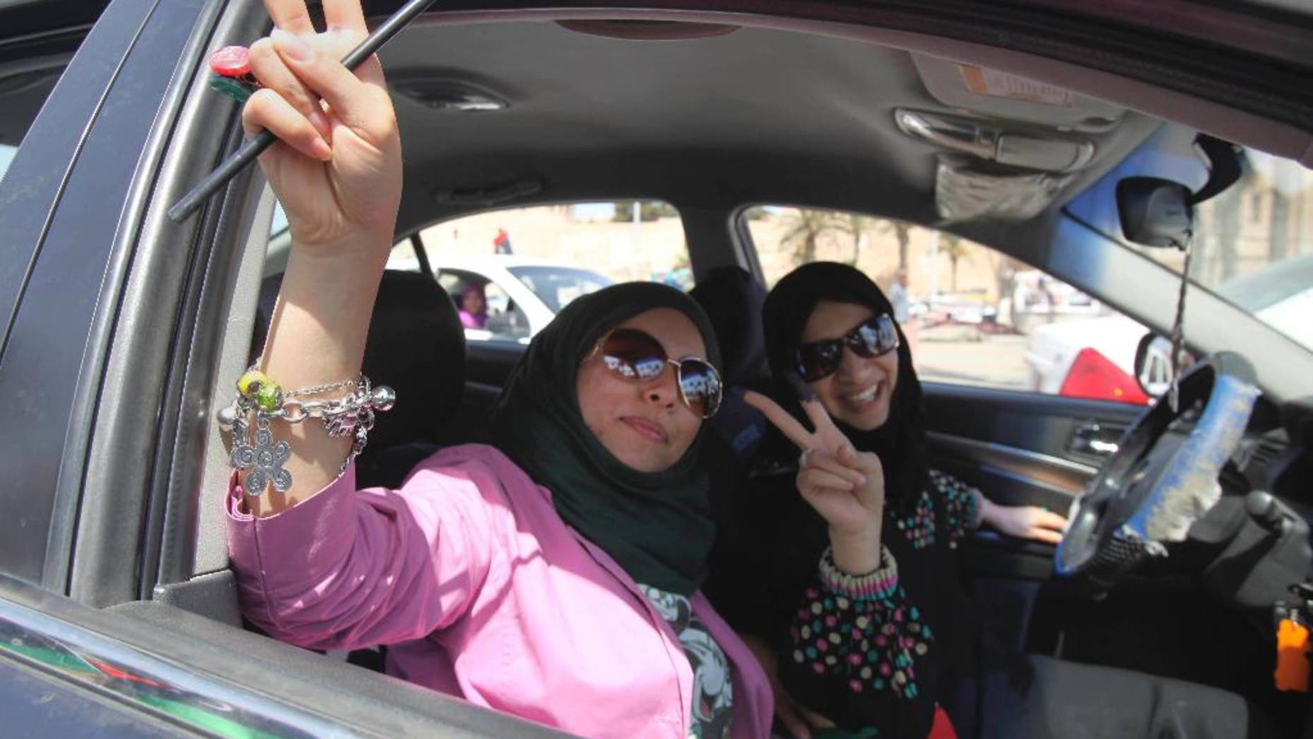 FILE -- In this July 7, 2012 file photo, Libyan women hold up their ink-marked fingers that shows they have voted as they drive in Tripoli, Libya. Eastern Libyan military authorities issued a ban Thursday, Feb. 16, 2017, on women from traveling outside the country without a male guardian, sparking mockery. The decision was issued by the Libyan Chief of Staff Abdel-Razek al-Nadhouri, the military ruler of eastern Libya. He was appointed by the army chief Khalifa Hifter who is allied with the internationally-recognized parliament. (AP Photo/Abdel Magid Al Fergany, File)