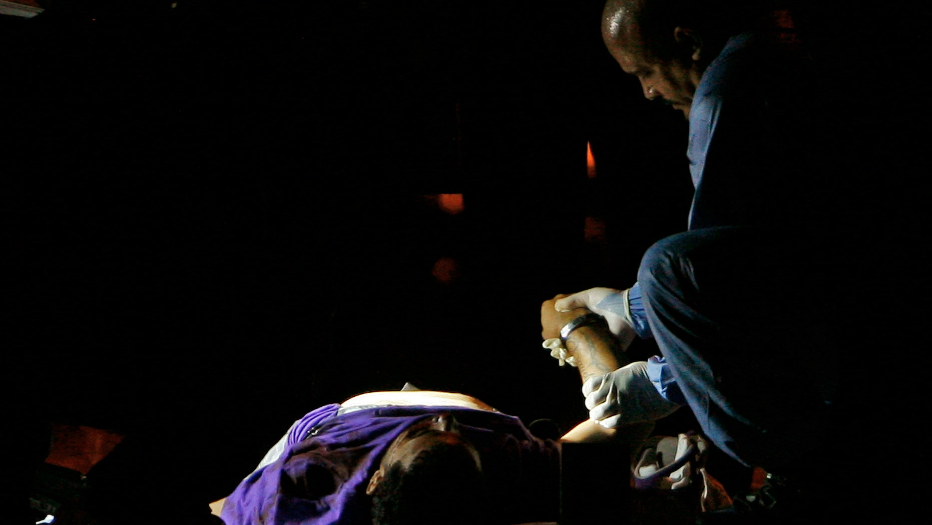 Oct. 2: A forensic investigator examines the body of a men killed by unidentified gunmen at a crime scene in Carolina, Puerto Rico.  (AP Photo/Ricardo Arduengo)