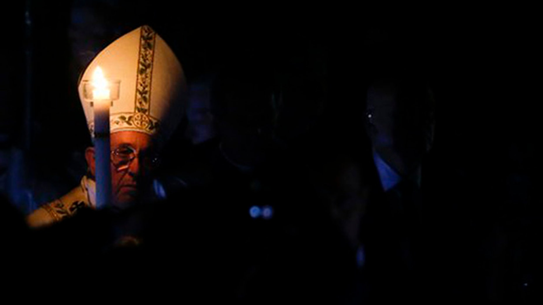 Pope Francis holds a white candle as he arrives for an Easter vigil service, in St. Peter's Basilica, at the Vatican, Saturday, March 26, 2016. (AP Photo/Gregorio Borgia)