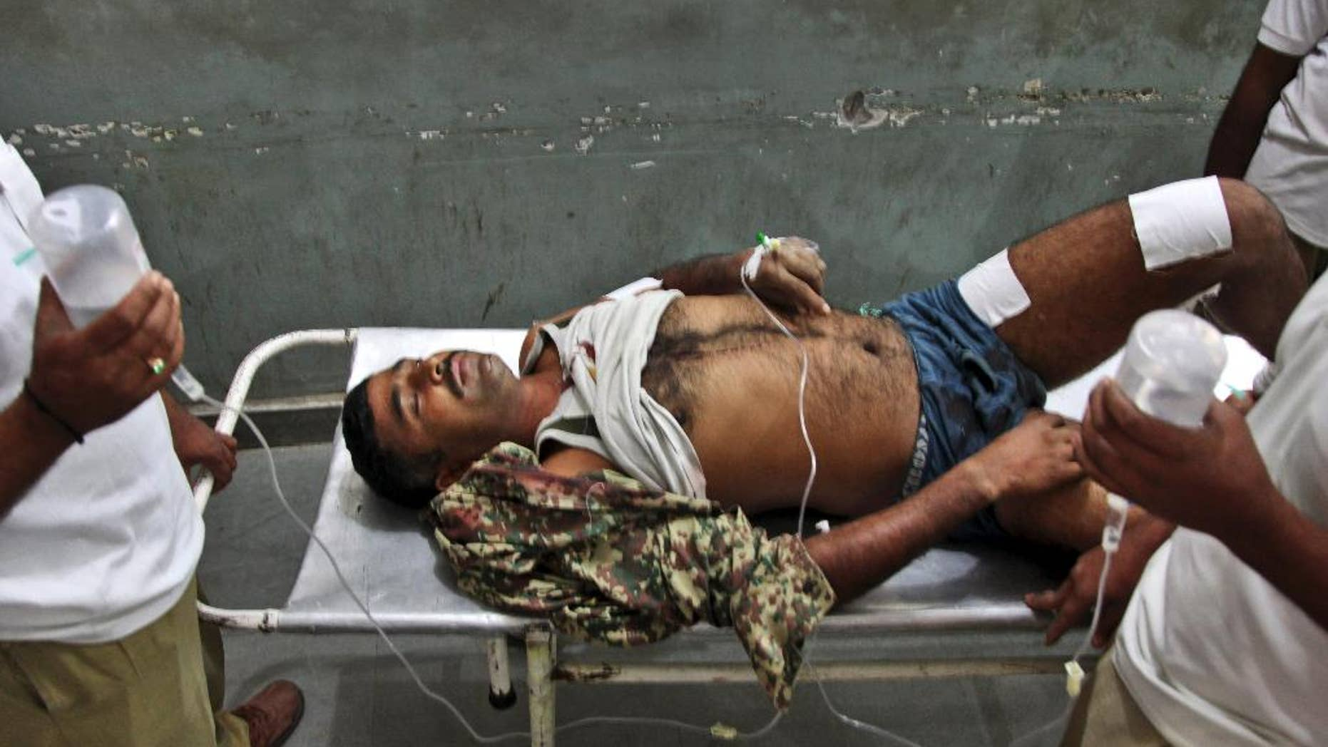 An Indian Border Security Force soldier is carried on a stretcher for treatment at the Government Medical College Hospital after being injured in attacks between India-Pakistan firing at the border area in Ranbir Singh Pura, in Jammu, India, Thursday, Oct. 9, 2014. Troops trading heavy fire between Pakistan and Indian-controlled Kashmir plunged civilians on both sides into grief with many killed and wounded this week, prompting many to question how two nations committed to a 2003 cease-fire could be targeting civilians while trading blame about who started shooting first. (AP Photo/Channi Anand)