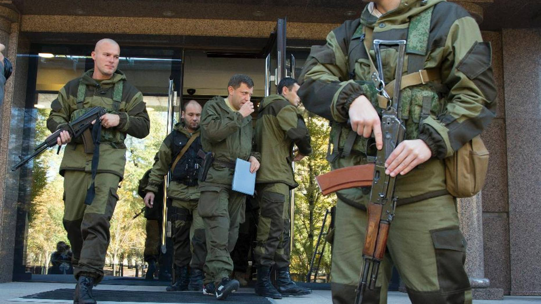 Alexander Zakharchenko, Prime Minister of the self proclaimed 'Donetsk People's Republic', centre,  surrounded by pro-Russian rebels, walks in the town of Donetsk, eastern Ukraine Saturday, Oct. 11, 2014. A pro-Russian rebel leader says they have signed a demarcation deal with the Ukrainian government which sees the Ukrainians give up several villages including the one next to a strategic airport. (AP Photo/Dmitry Lovetsky)