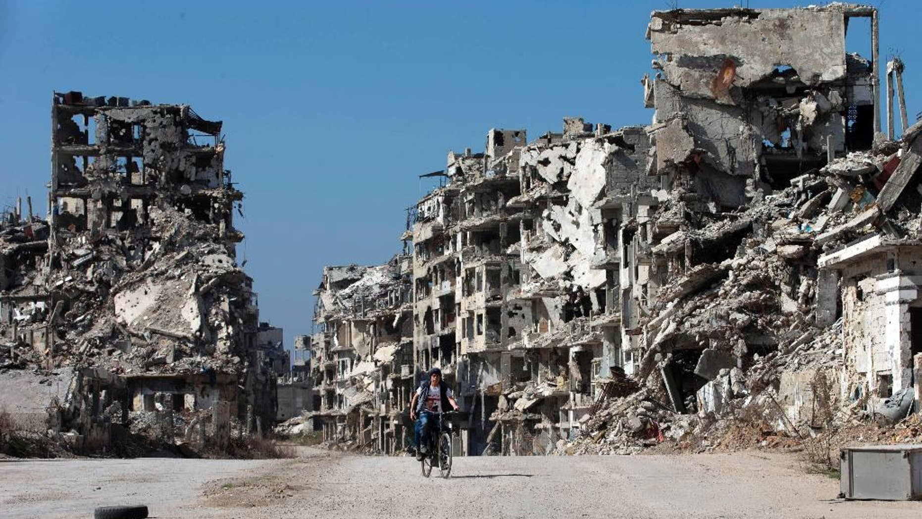 FILE -- In this February 26, 2016, file photo, a Syrian boy rides a bicycle through a devastated part of the old city of Homs, Syria. Syrian opposition fighters will be allowed to leave the last rebel-held neighborhood in the city of Homs under a Russia-backed deal signed on Monday, March 13, 2017, a Syrian official and an activist said.(AP Photo/Hassan Ammar, File)