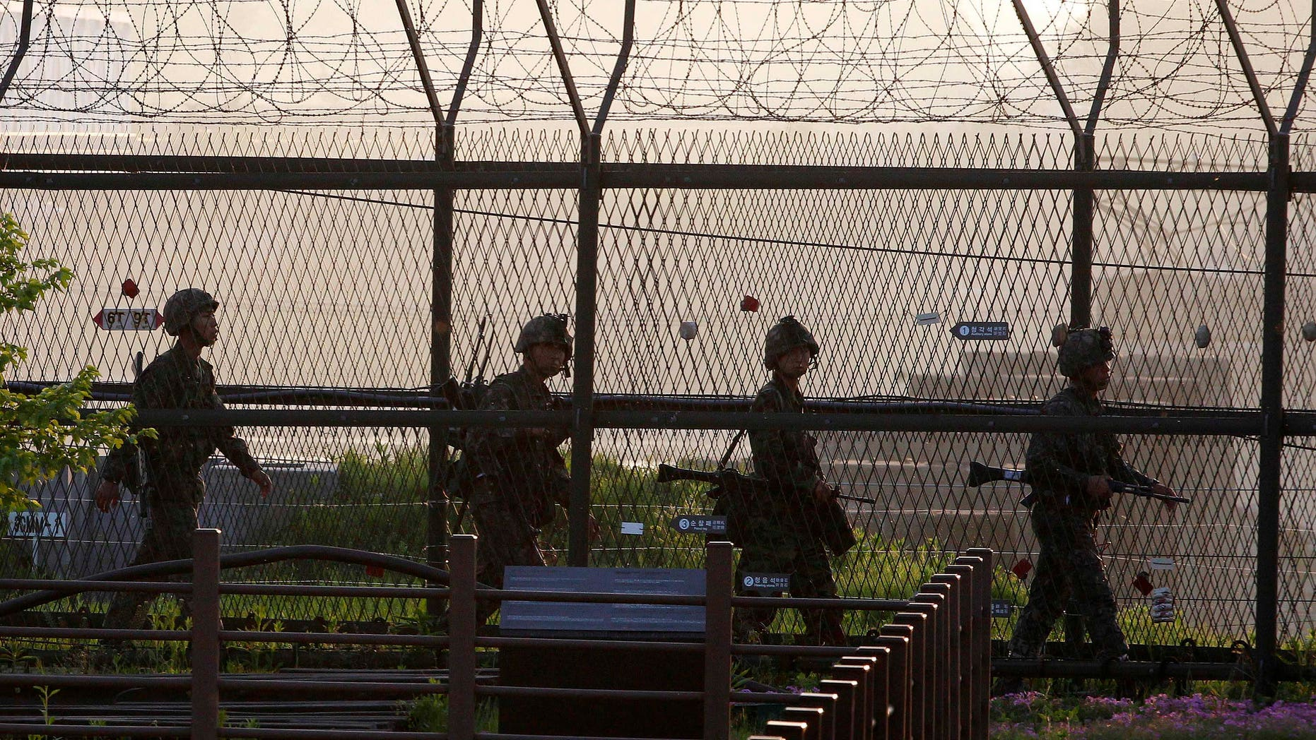 South Korean Army soldiers patrol along a barbed-wire fence near the border village of the Panmunjom in Paju, South Korea, Monday, May 20, 2103. North Korea fired short-range projectiles into its own eastern waters Monday for a third straight day, Seoul officials said. The North said it was bolstering deterrence against enemy attack. (AP Photo/Ahn Young-joon)
